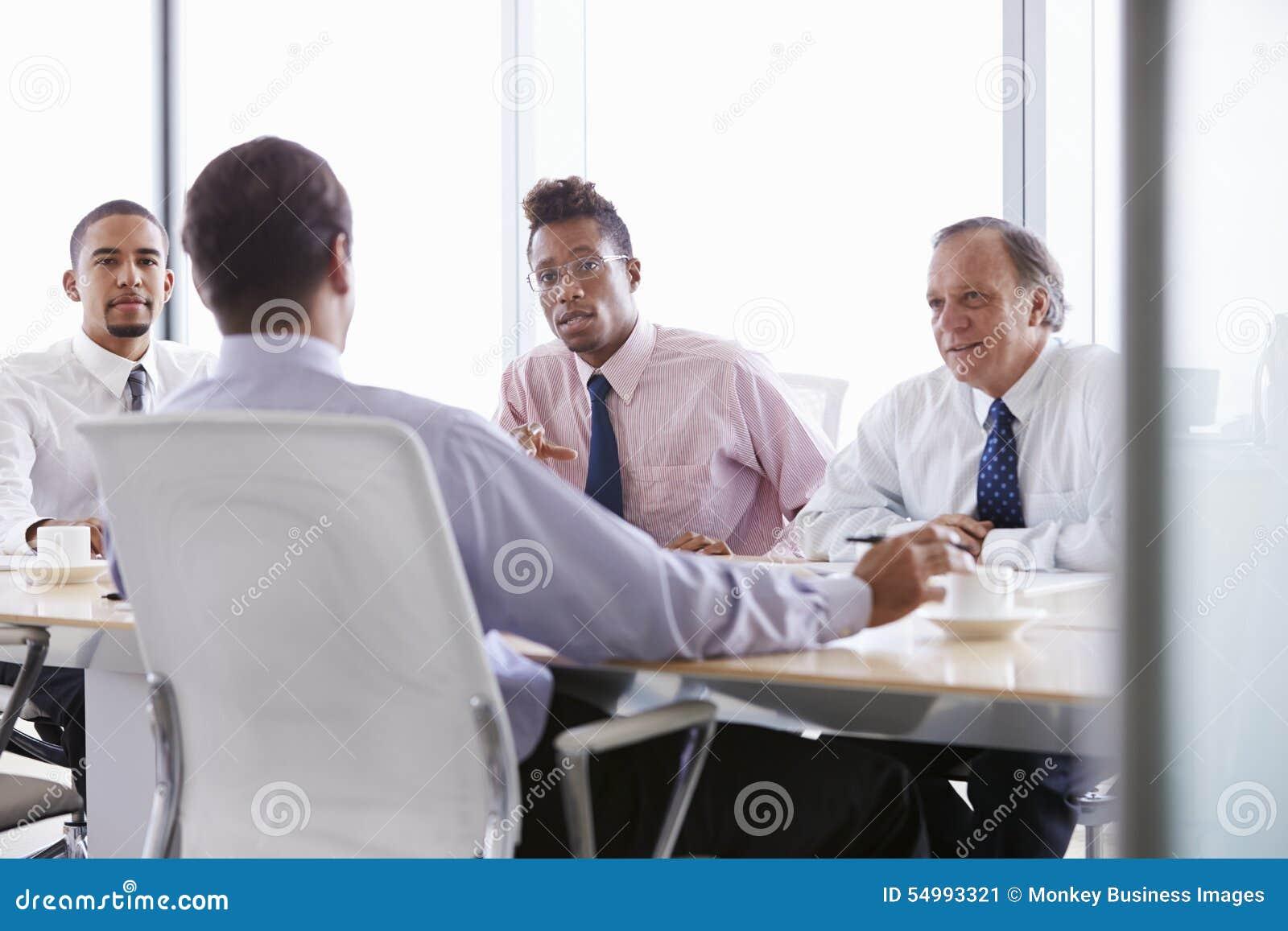 Τέσσερις επιχειρηματίες που διοργανώνουν τη συνεδρίαση γύρω από τον πίνακα αιθουσών συνεδριάσεων