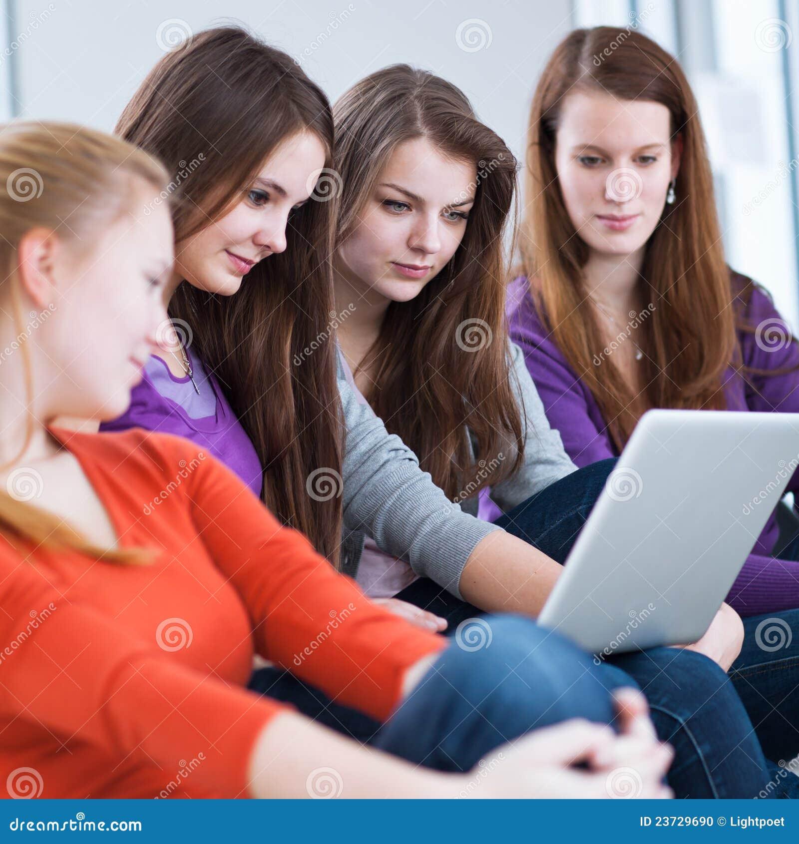 Τέσσερις θηλυκοί φοιτητές πανεπιστημίου που χρησιμοποιούν ένα lap-top