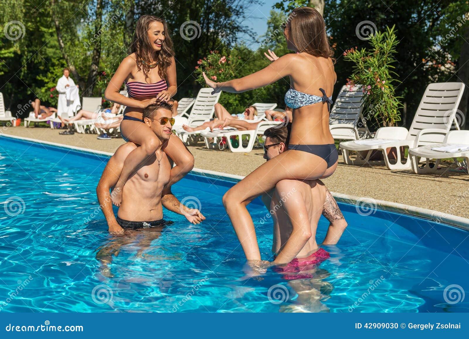 Τέσσερις φίλοι που έχουν τη διασκέδαση στην πισίνα