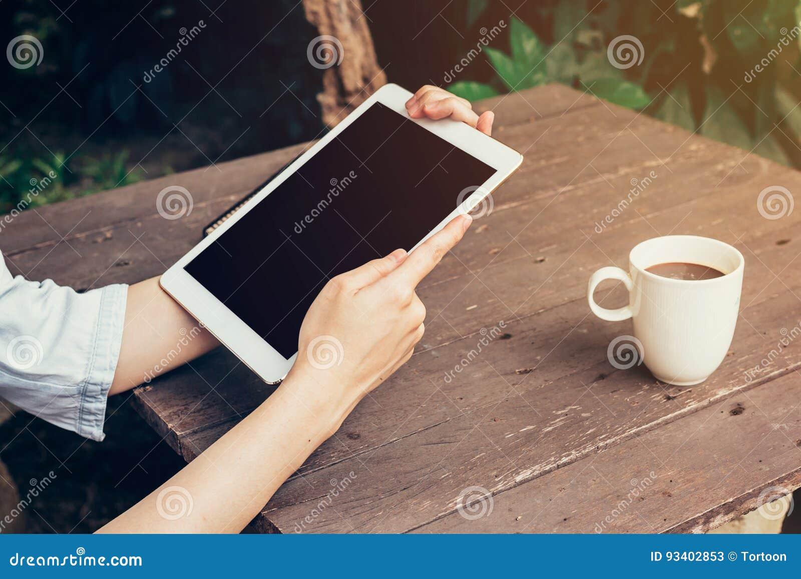 Ταμπλέτα εκμετάλλευσης χεριών γυναικών και κενή επίδειξη οθόνης στον ξύλινο πίνακα