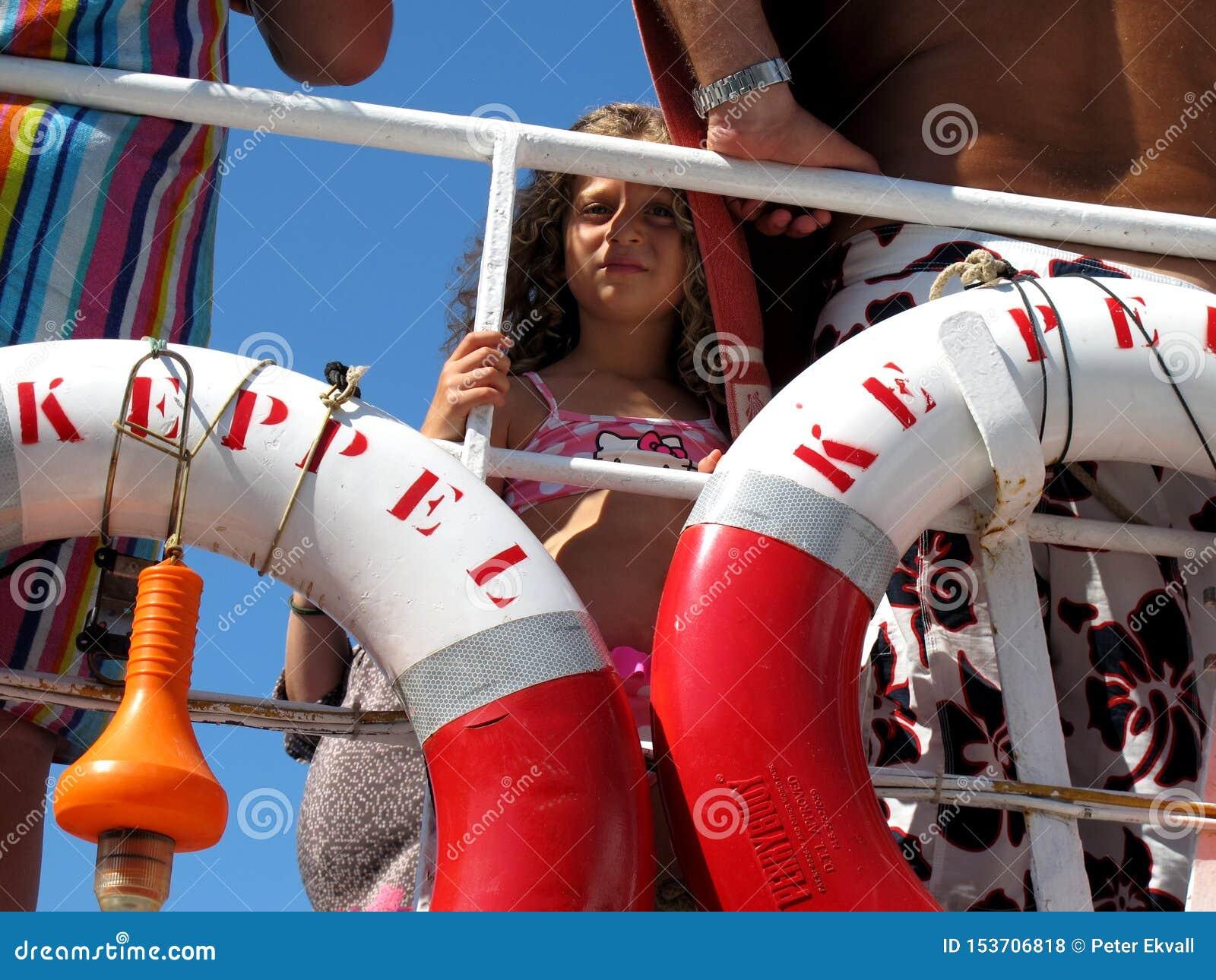 Ταξίδι βαρκών με το κοίταγμα μικρών κοριτσιών μέσω των lifebuoys