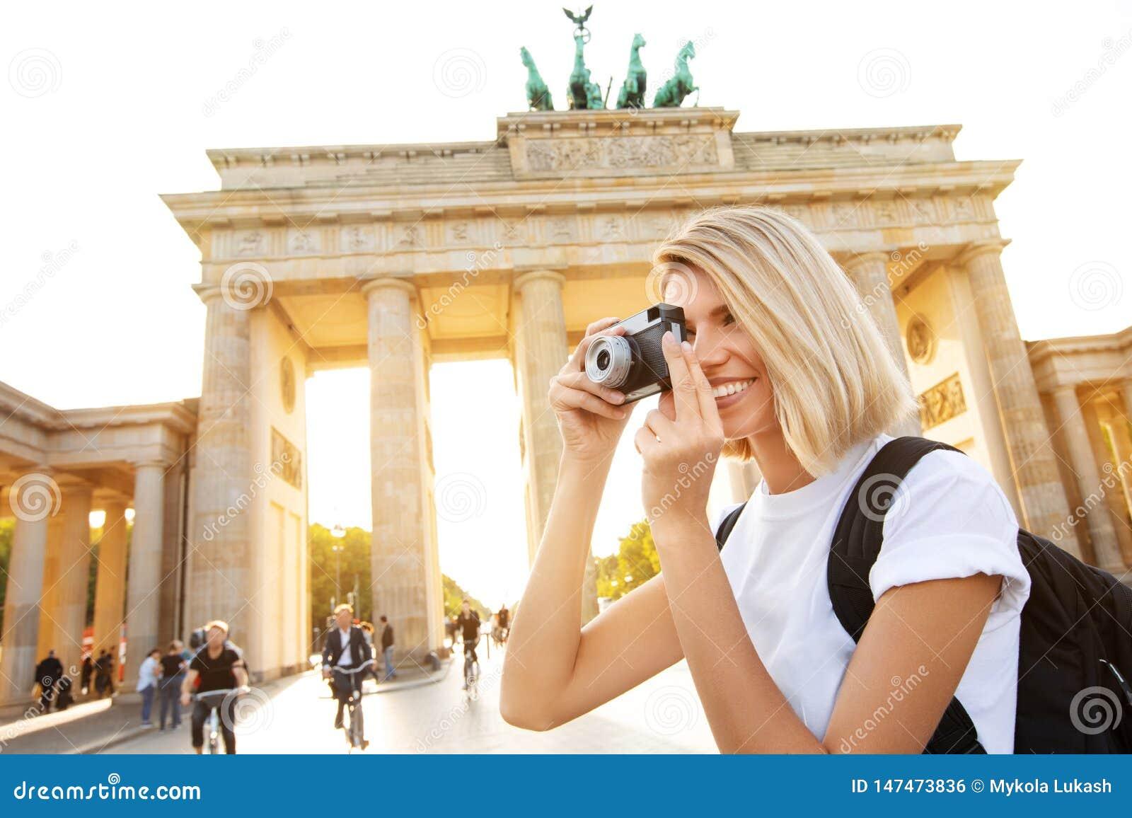 Ταξίδι στο Βερολίνο, ευτυχής γυναίκα τουριστών με τη κάμερα μπροστά από την πύλη του Βραδεμβούργου, Βερολίνο, Γερμανία