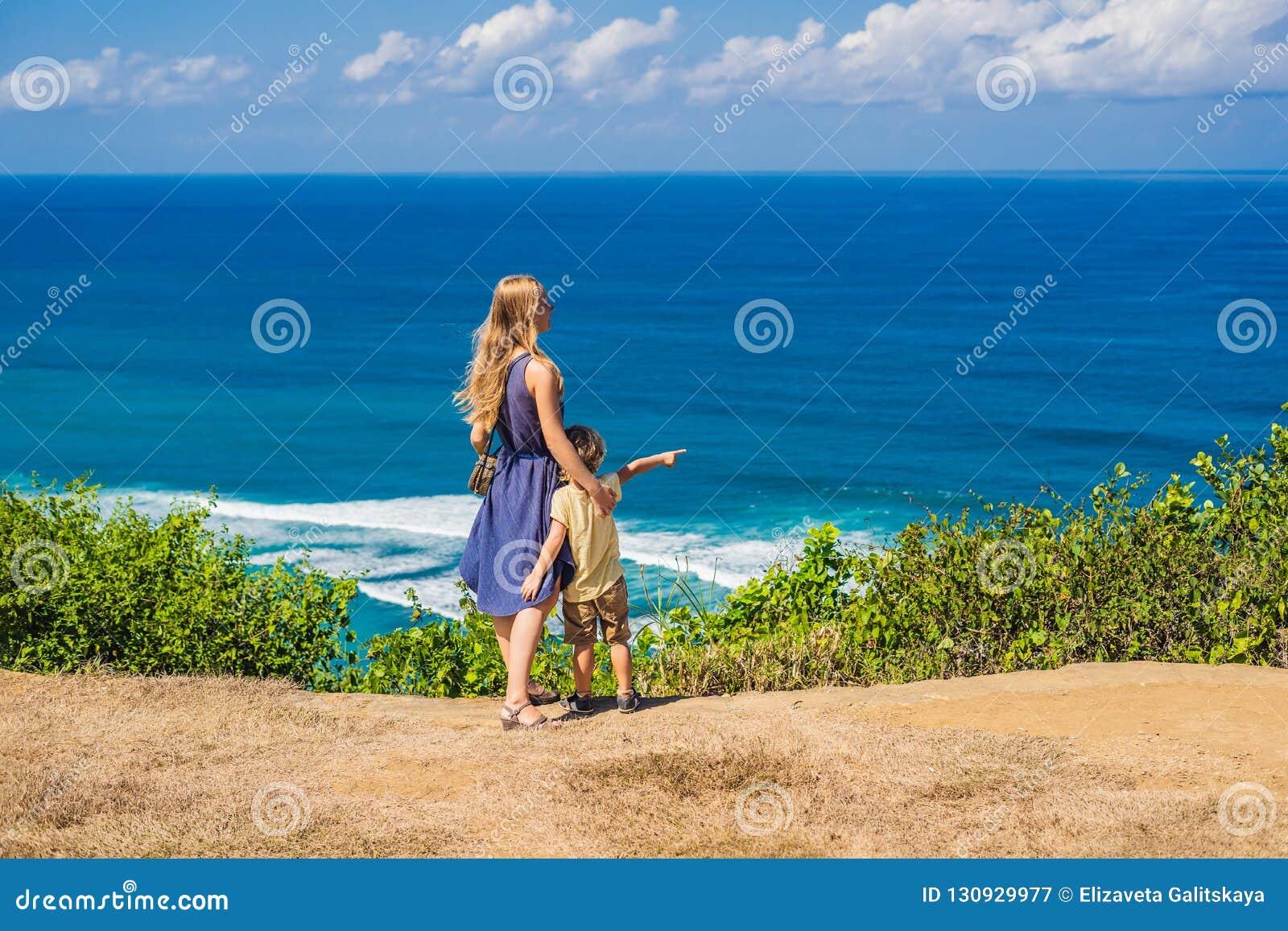Ταξιδιώτες Mom και γιων σε έναν απότομο βράχο επάνω από την παραλία Κενός παράδεισος