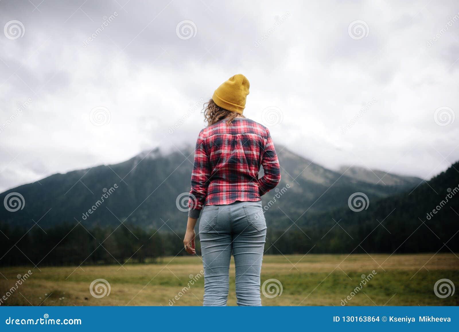 Ταξιδιώτης γυναικών που στέκεται να δει τα βουνά ορεινών περιοχών