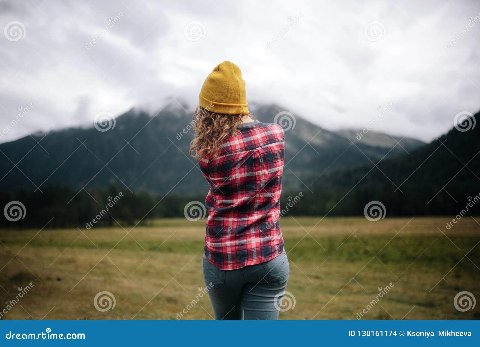 ταξιδιώτης κοριτσιών στο καπέλο με το σακίδιο πλάτης που εξετάζει τα σύννεφα στα βουνά