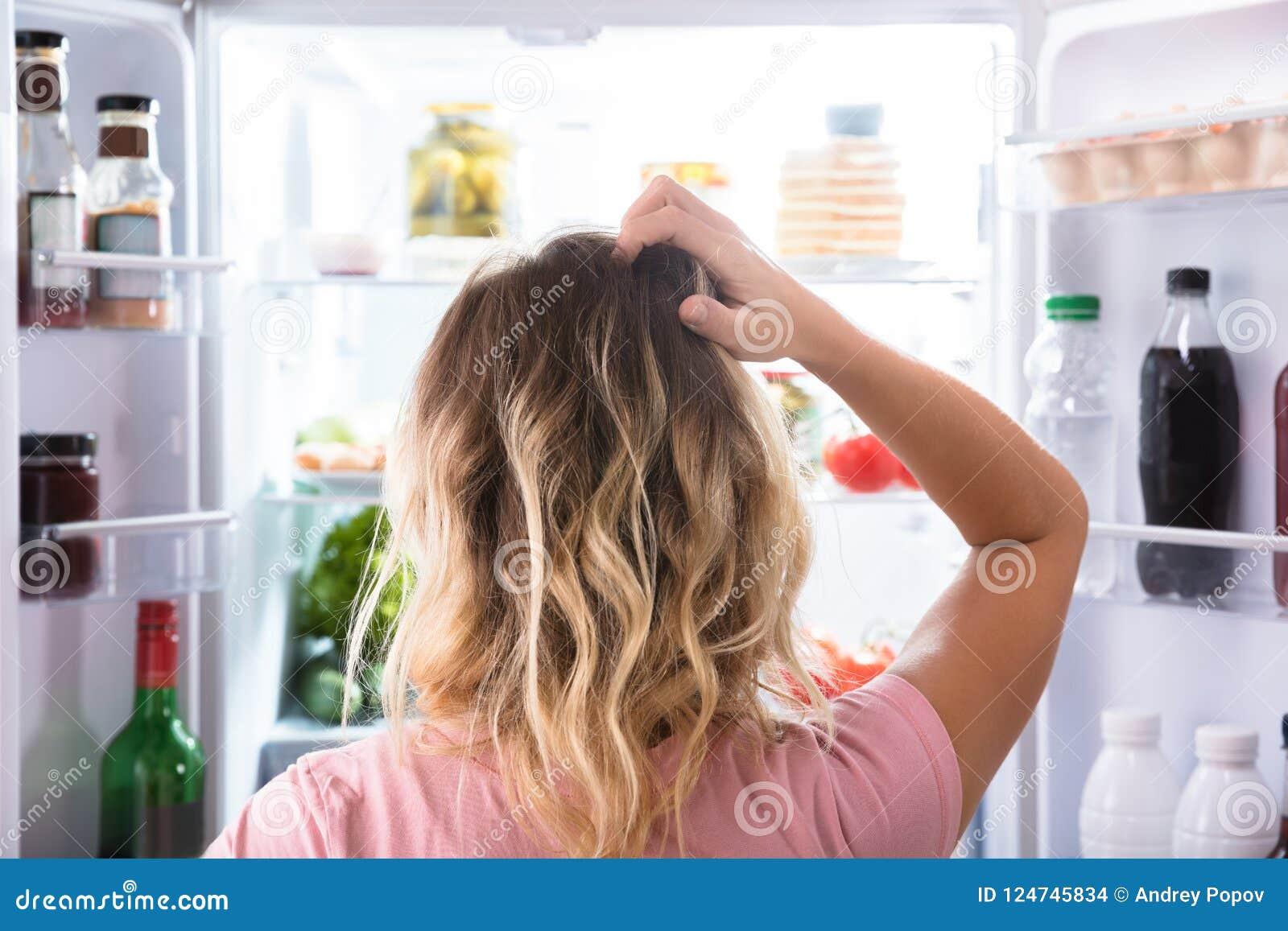 Ταραγμένη γυναίκα που κοιτάζει στο ανοικτό ψυγείο