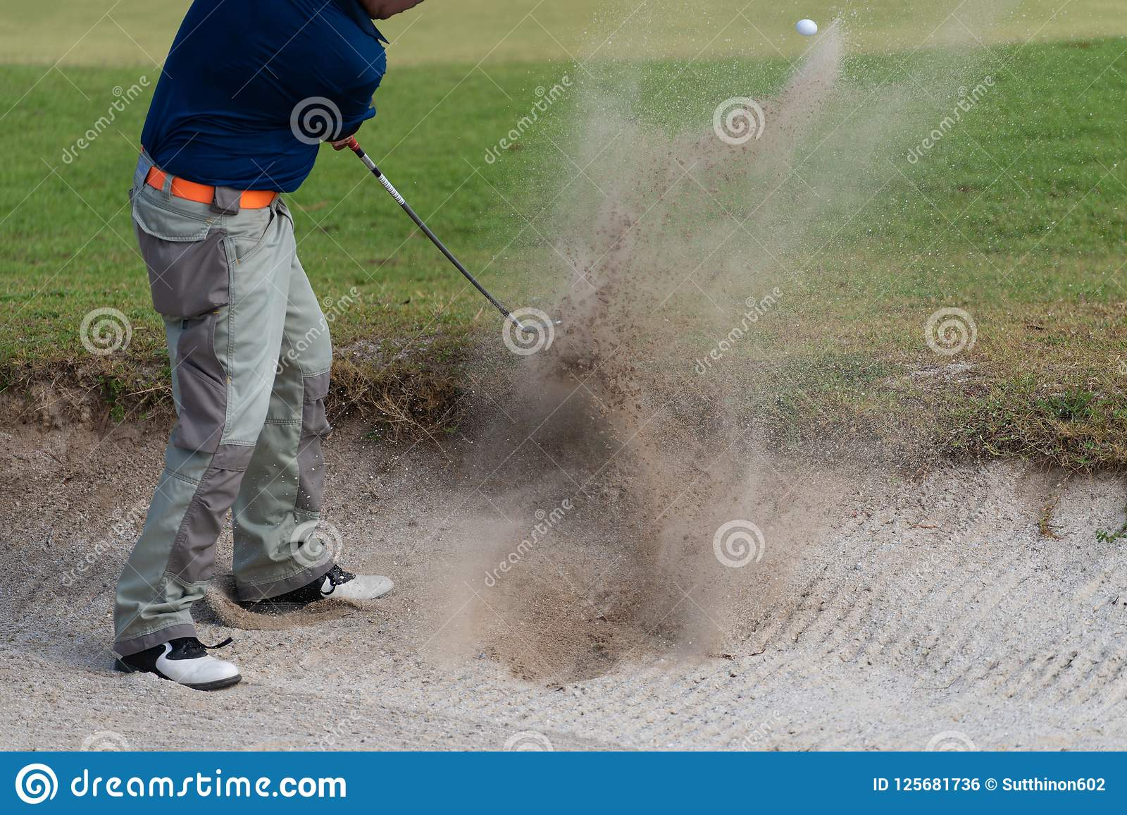 Ταϊλανδικός φορέας γκολφ νεαρών άνδρων στην ταλάντευση δράσης στο κοίλωμα άμμου κατά τη διάρκεια της πρακτικής πριν από τα πρωταθ