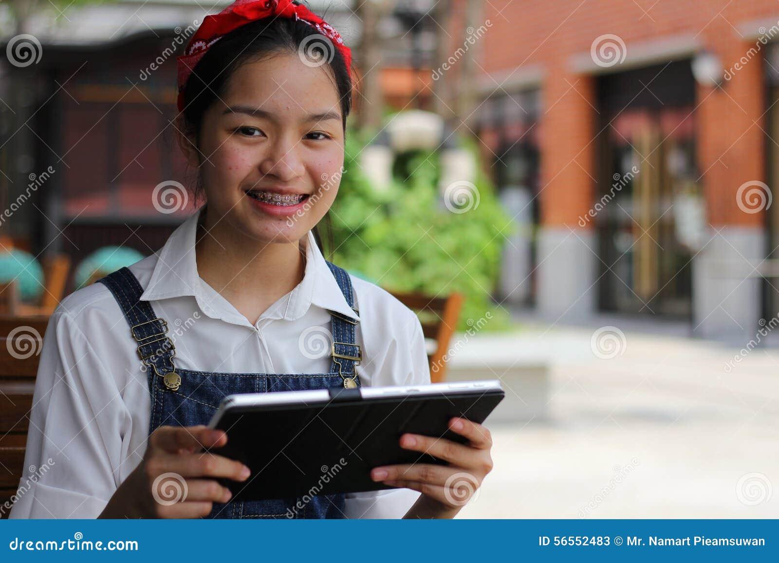 Download Ταϊλανδικό όμορφο κορίτσι εφήβων σπουδαστών που χρησιμοποιεί την ταμπλέτα της Στοκ Εικόνα - εικόνα από πάρκο, κορίτσι: 56552483
