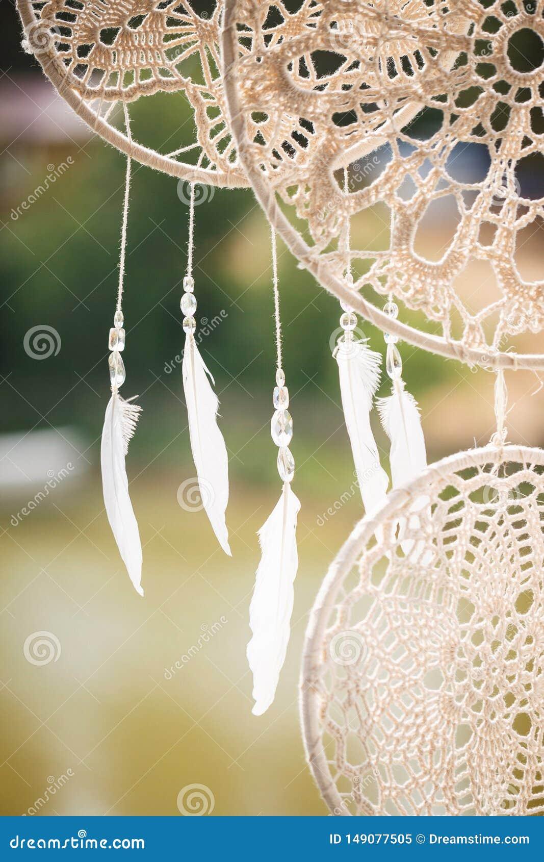 Τα άσπρα ελαφριά φτερά κρεμούν στα νήματα με τις διαφανείς χάντρες Στρογγυλά dreamcatchers από το macrame