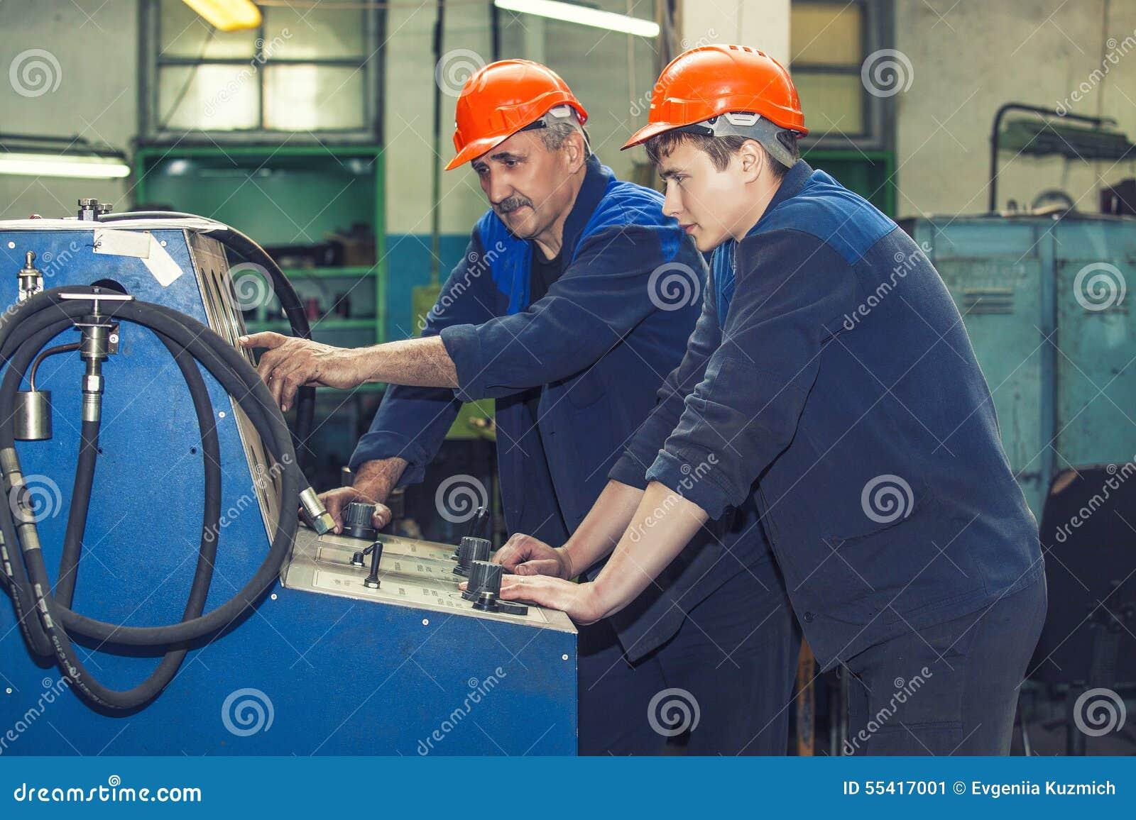Τα άτομα εργάζονται στο παλαιό εργοστάσιο για την εγκατάσταση του εξοπλισμού