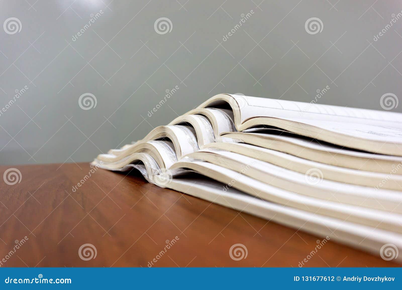 Τα ανοικτά περιοδικά βρίσκονται το ένα πάνω από το άλλο σε έναν καφετή πίνακα, τα έγγραφα είναι συσσωρευμένη κινηματογράφηση σε π
