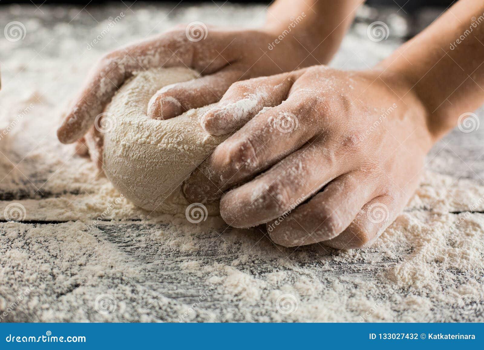 Τα αρσενικά χέρια αρχιμαγείρων ζυμώνουν τη ζύμη με το αλεύρι στον πίνακα κουζινών