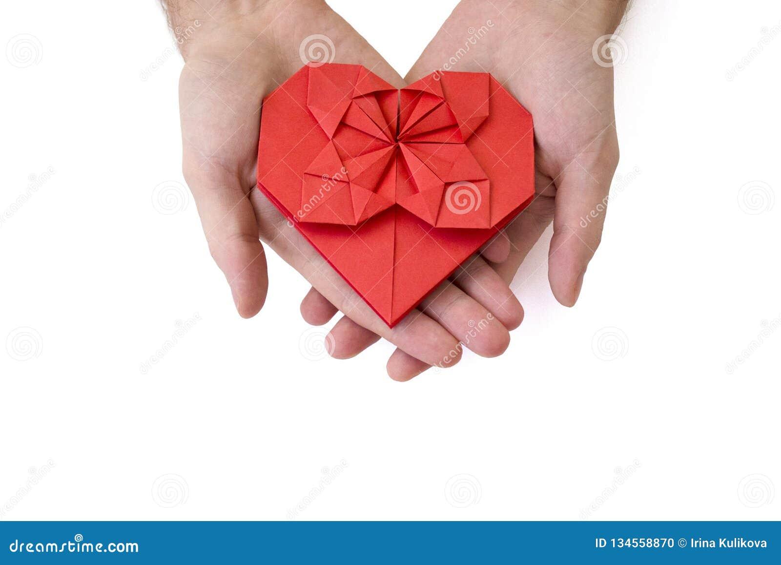 Τα αρσενικά χέρια κρατούν μια κόκκινη καρδιά εγγράφου γίνοντη στην τεχνική origami απομονωμένος Έννοια της αγάπης, εορτασμός, προ