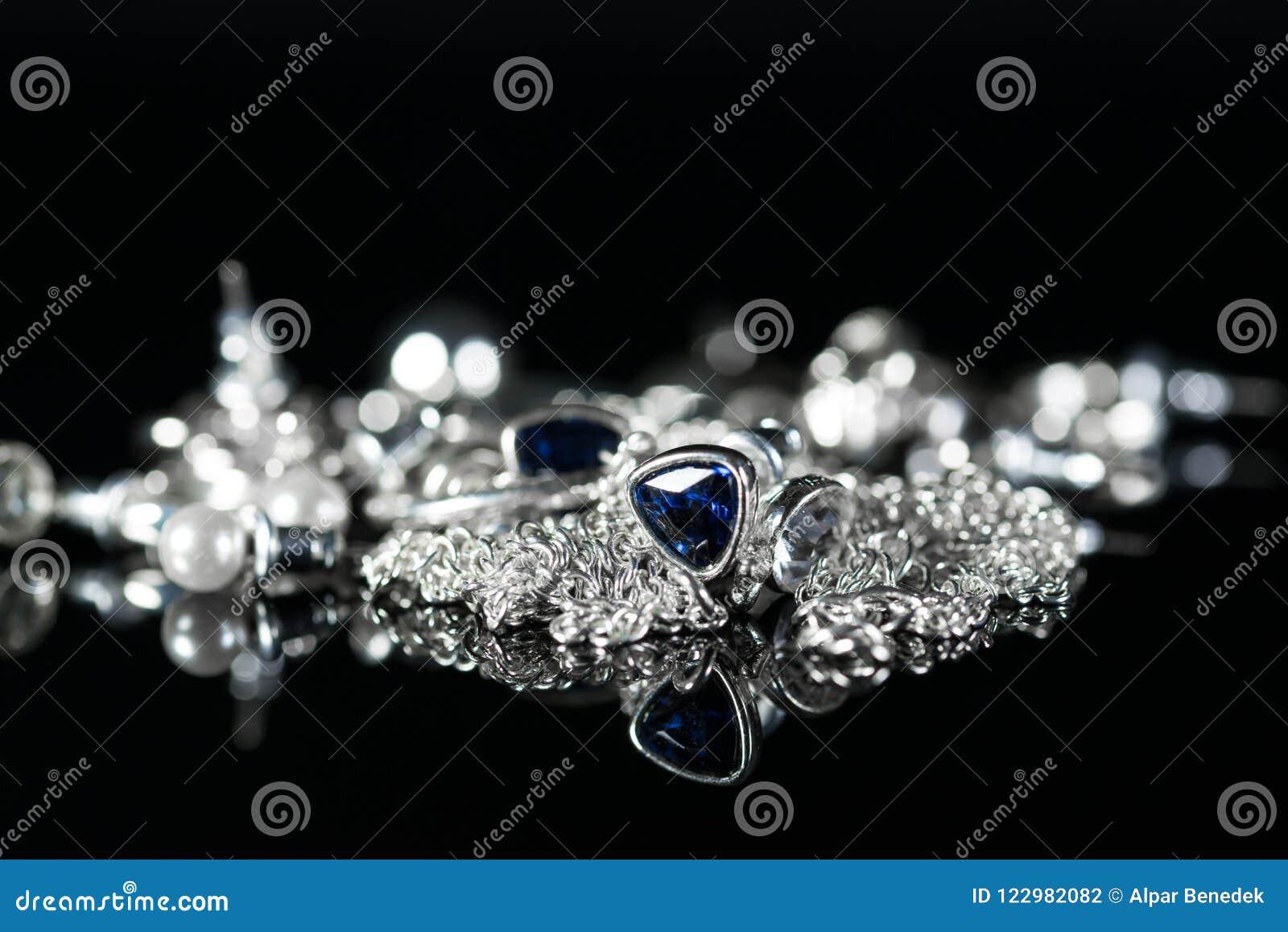 Τα ασημένια δαχτυλίδια αυτιών κοσμήματος, αλυσίδα, δαχτυλίδια κλείνουν αυξημένος
