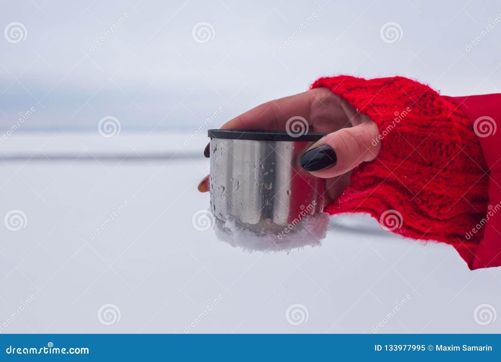 Τα ασημένια thermos με τον καφέ ή το τσάι είναι στο χιόνι στη χιονισμένη όχθη ποταμού υποβάθρου
