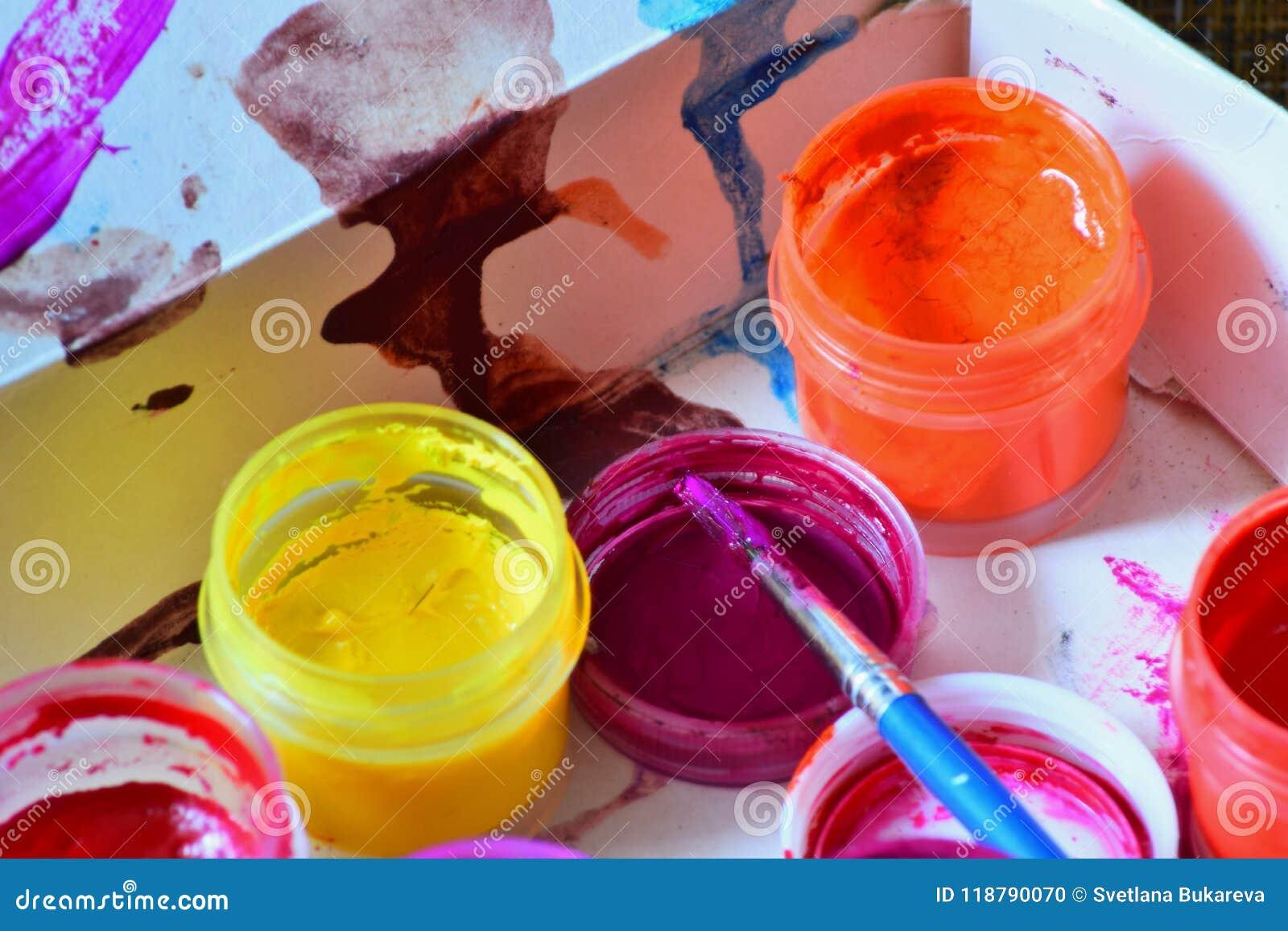 Τα βάζα με τα ζωηρόχρωμα φωτεινά χρώματα και μια βούρτσα προετοιμάζονται για την εργασία καλλιτεχνών ` s