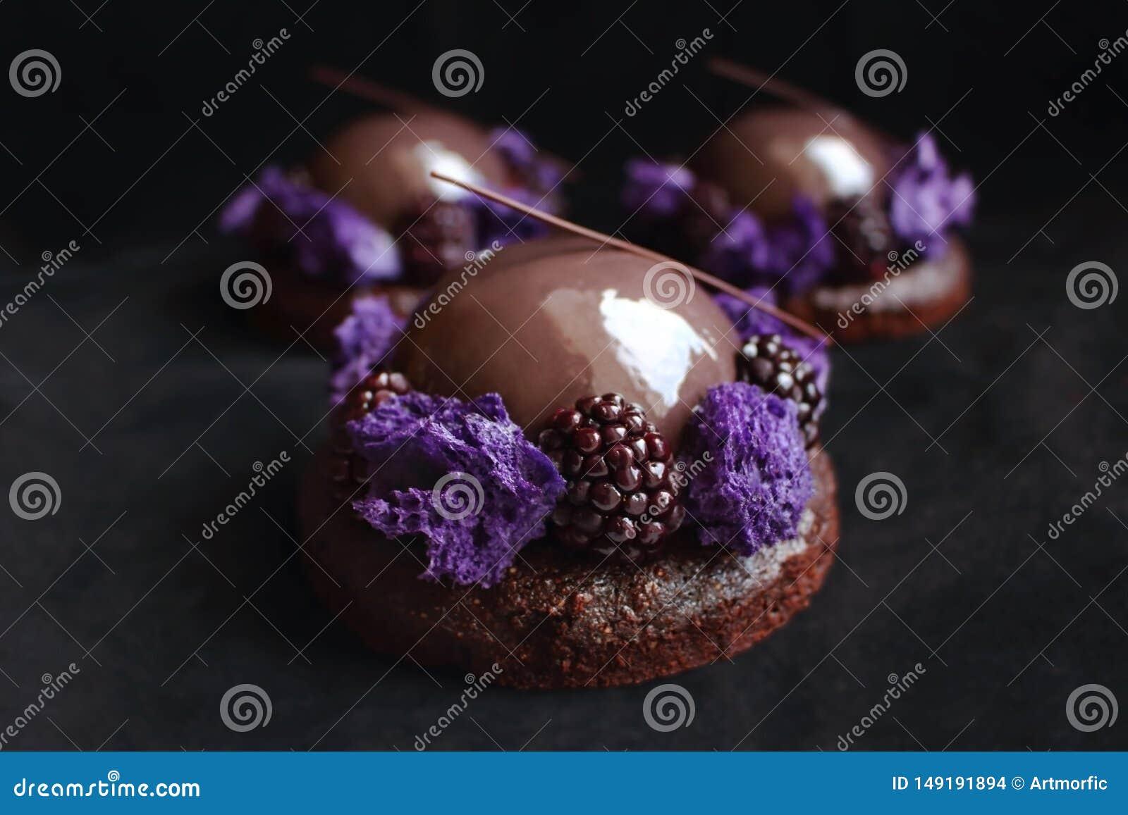 Τα βερνικωμένα επιδόρπια σοκολάτας και βατόμουρων με το πορφυρό μικρόκυμα σφουγγίζουν και φρέσκα μούρα στο μαύρο υπόβαθρο βελούδο