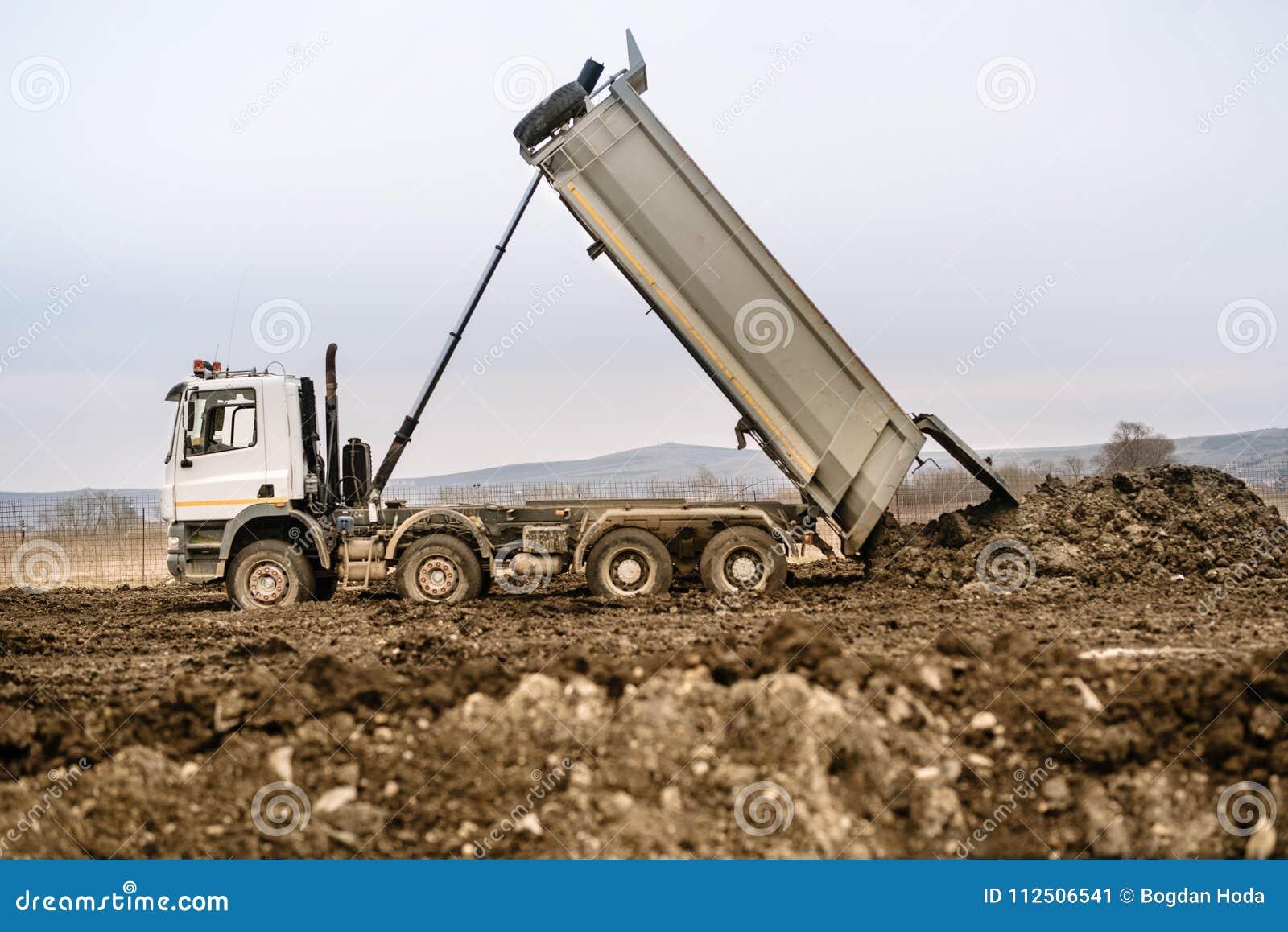 Τα βιομηχανικά Η.Ε φορτηγών εκφορτωτών που φορτώνουν το αμμοχάλικο και τη γη στο εργοτάξιο οικοδομής εθνικών οδών