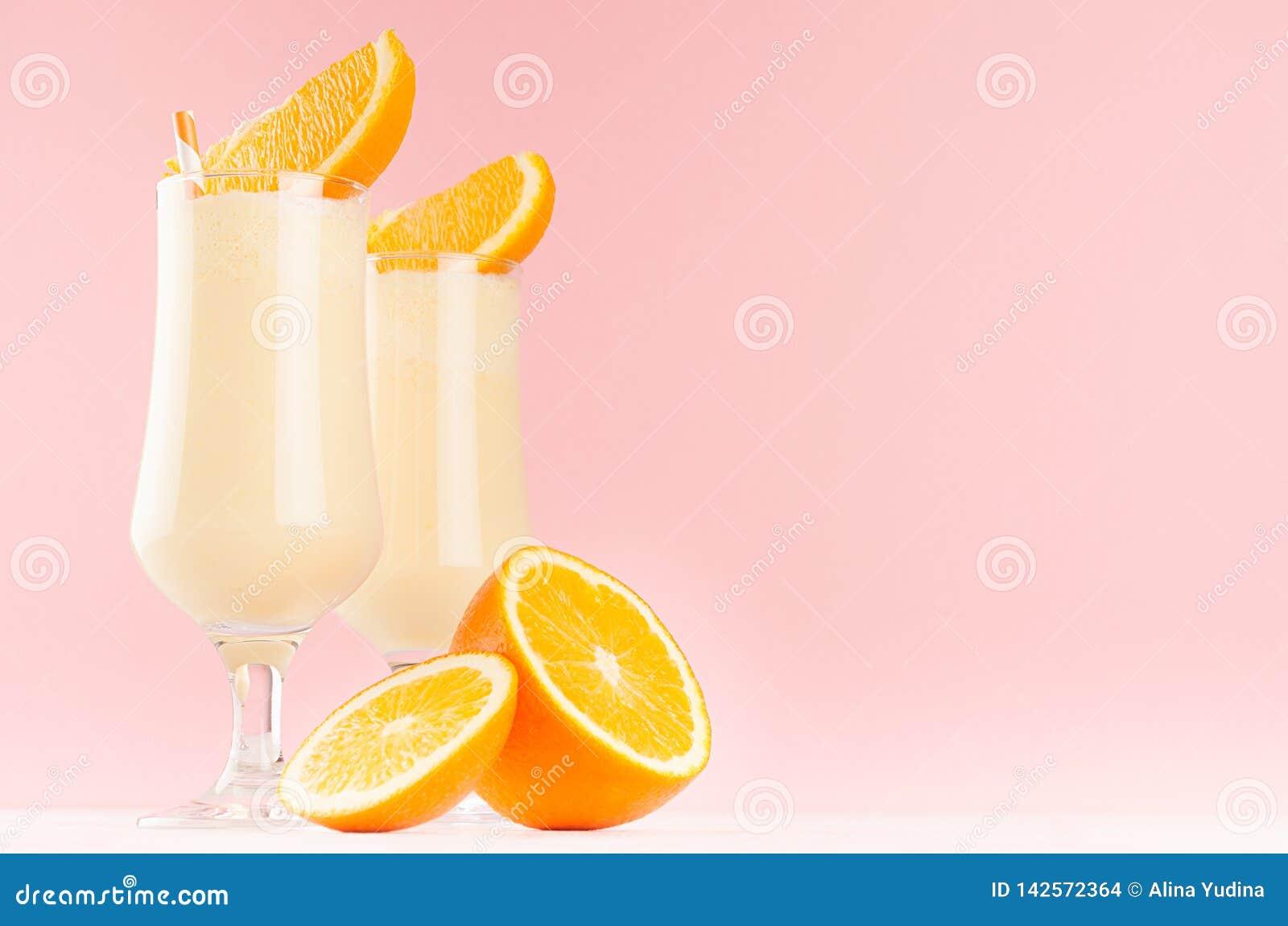Τα γλυκά εύθυμα milkshakes διακόσμησαν τα φρούτα φετών, ριγωτά άχυρα στο ελαφρύ ρόδινο υπόβαθρο κρητιδογραφιών