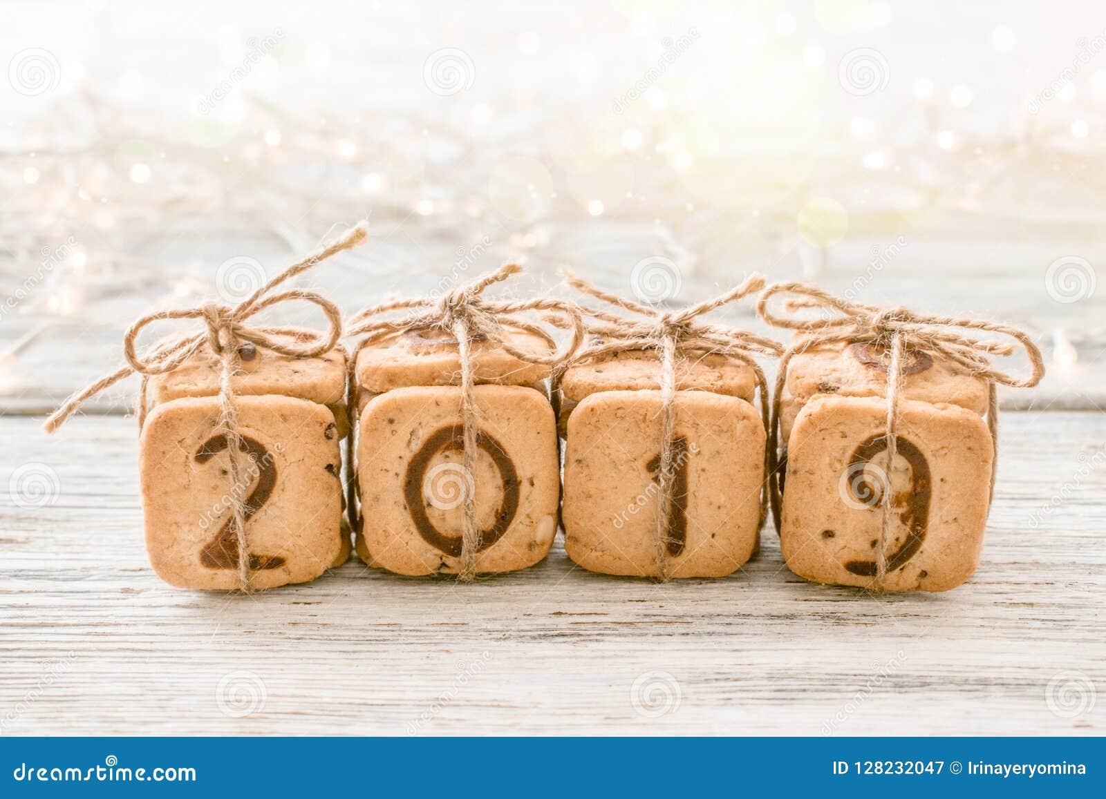 Τα εορταστικά ψηφία το 2019 Χριστουγέννων δώρων έκαναν από τα μπισκότα στο άσπρο υπόβαθρο με τα φω τα και bokeh Εύγευστο γλυκό co