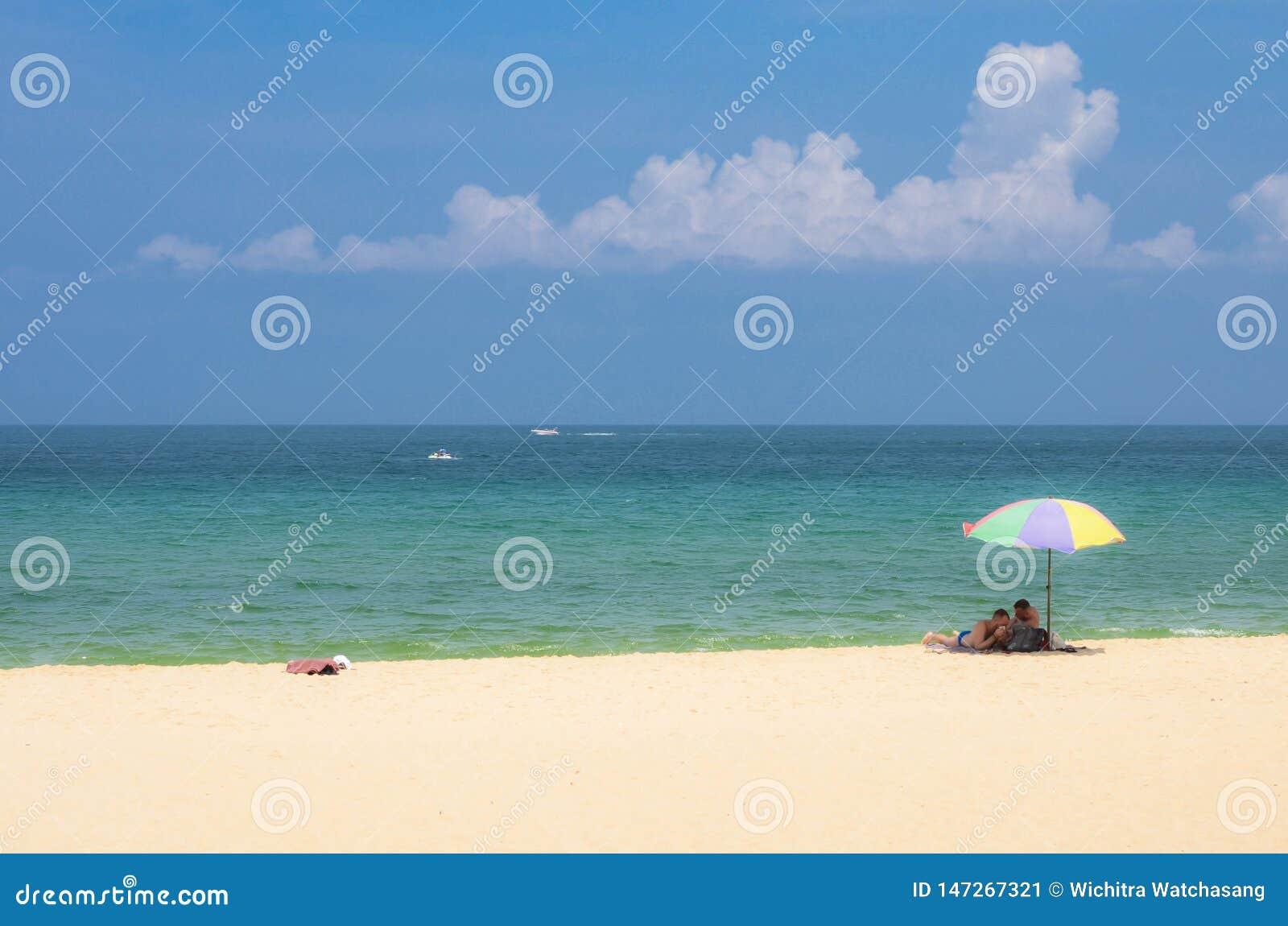 Τα ευτυχή άτομα ζευγών κάτω από τη ζωηρόχρωμη ομπρέλα στηρίζονται στην όμορφη τροπική παραλία σε Phuket
