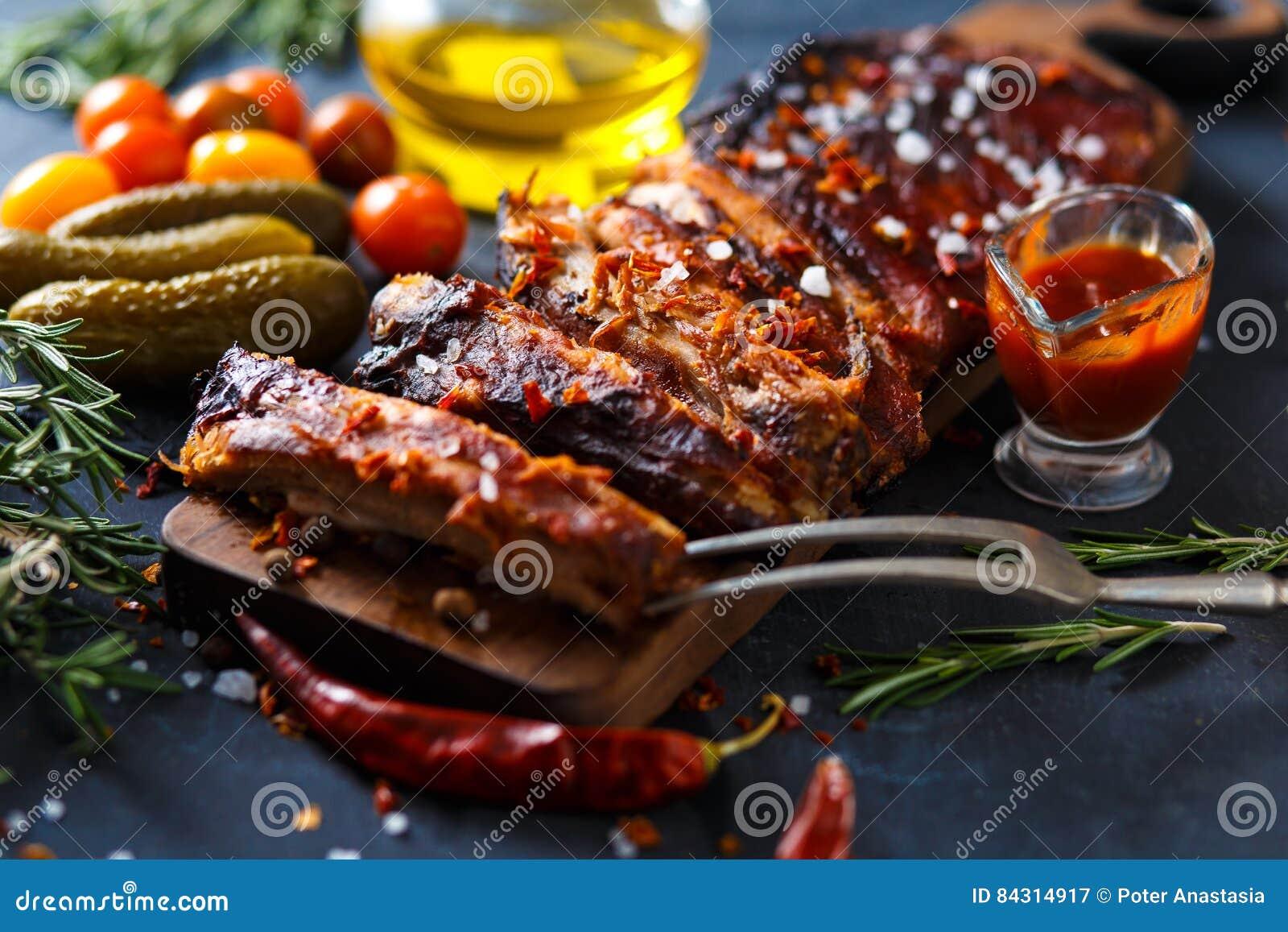 Τα εύγευστα ψημένα στη σχάρα πλευρά καρύκεψαν με μια πικάντικη σάλτσα ραντίσματος και εξυπηρέτησαν με τεμαχισμένος