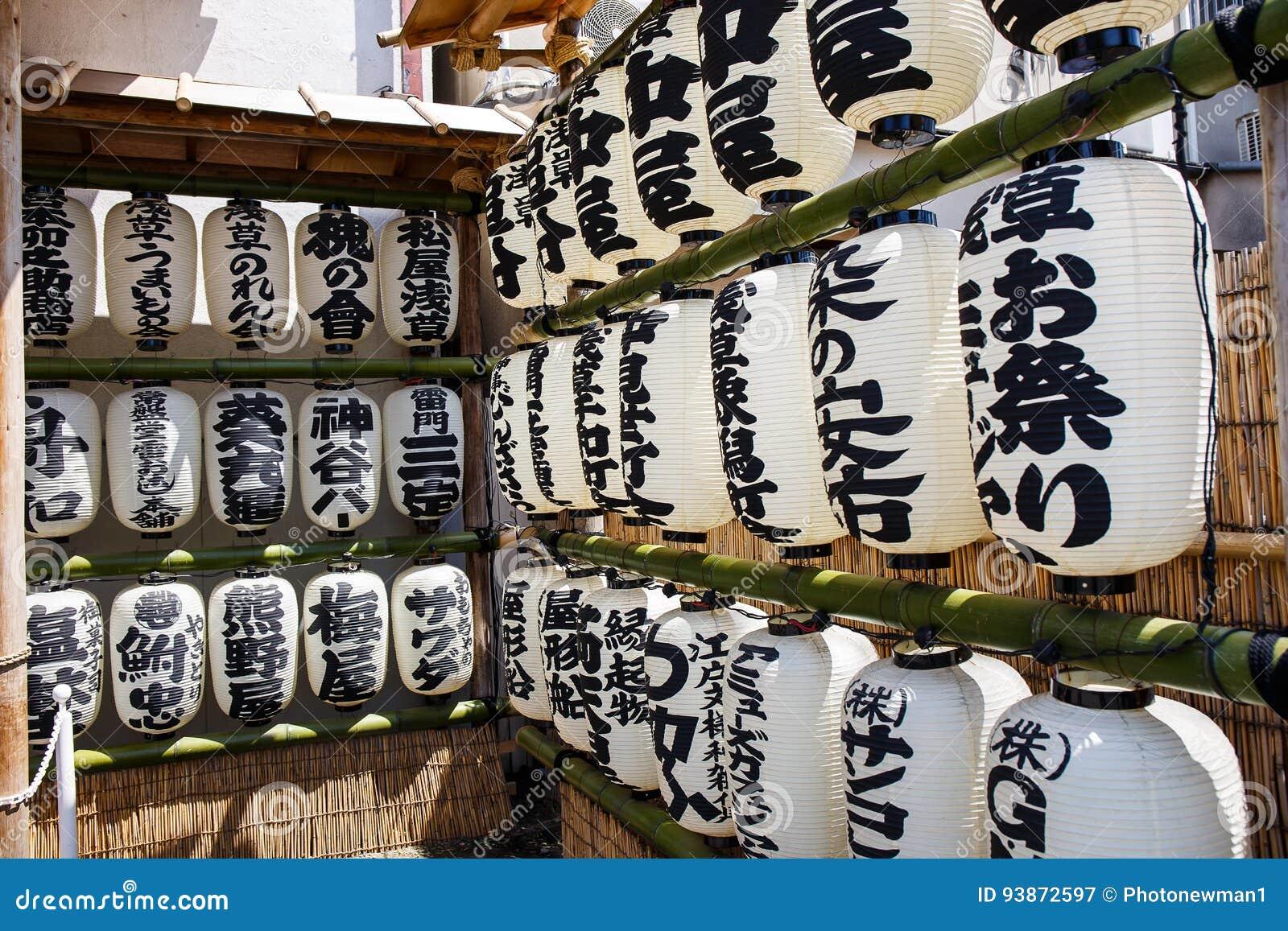 Τα ιαπωνικά φανάρια εγγράφου παράταξαν στα σύνολα μπαμπού με τις ιαπωνικές γραφές και κρεμούν εκτός από έναν ναό στο Τόκιο, Ιαπων