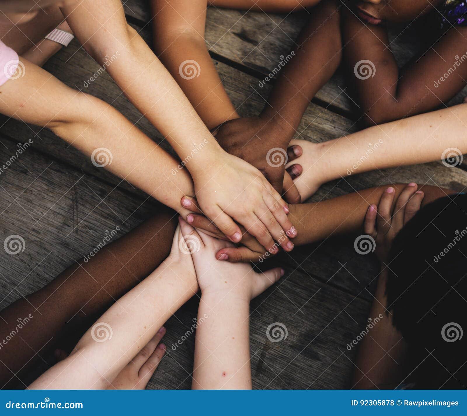 Τα διαφορετικά χέρια είναι ενώνουν μαζί στον ξύλινο πίνακα