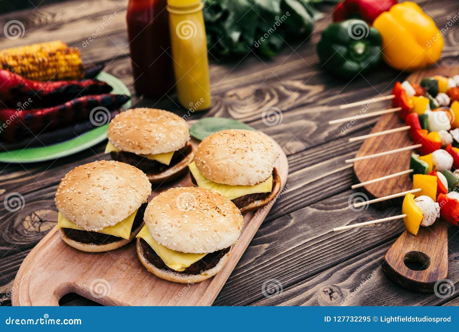 Τα καυτά εύγευστα burgers και τα λαχανικά που ψήνονται στη σχάρα για ψήνουν υπαίθρια
