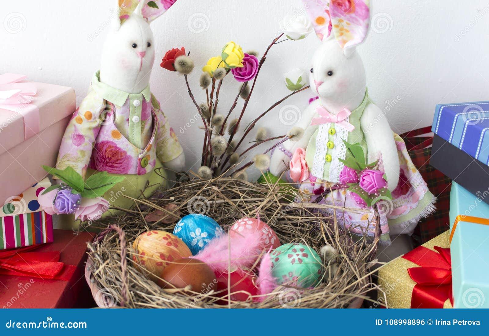 Τα κουνέλια εξετάζουν το καλάθι με τα ζωηρόχρωμα αυγά για Πάσχα