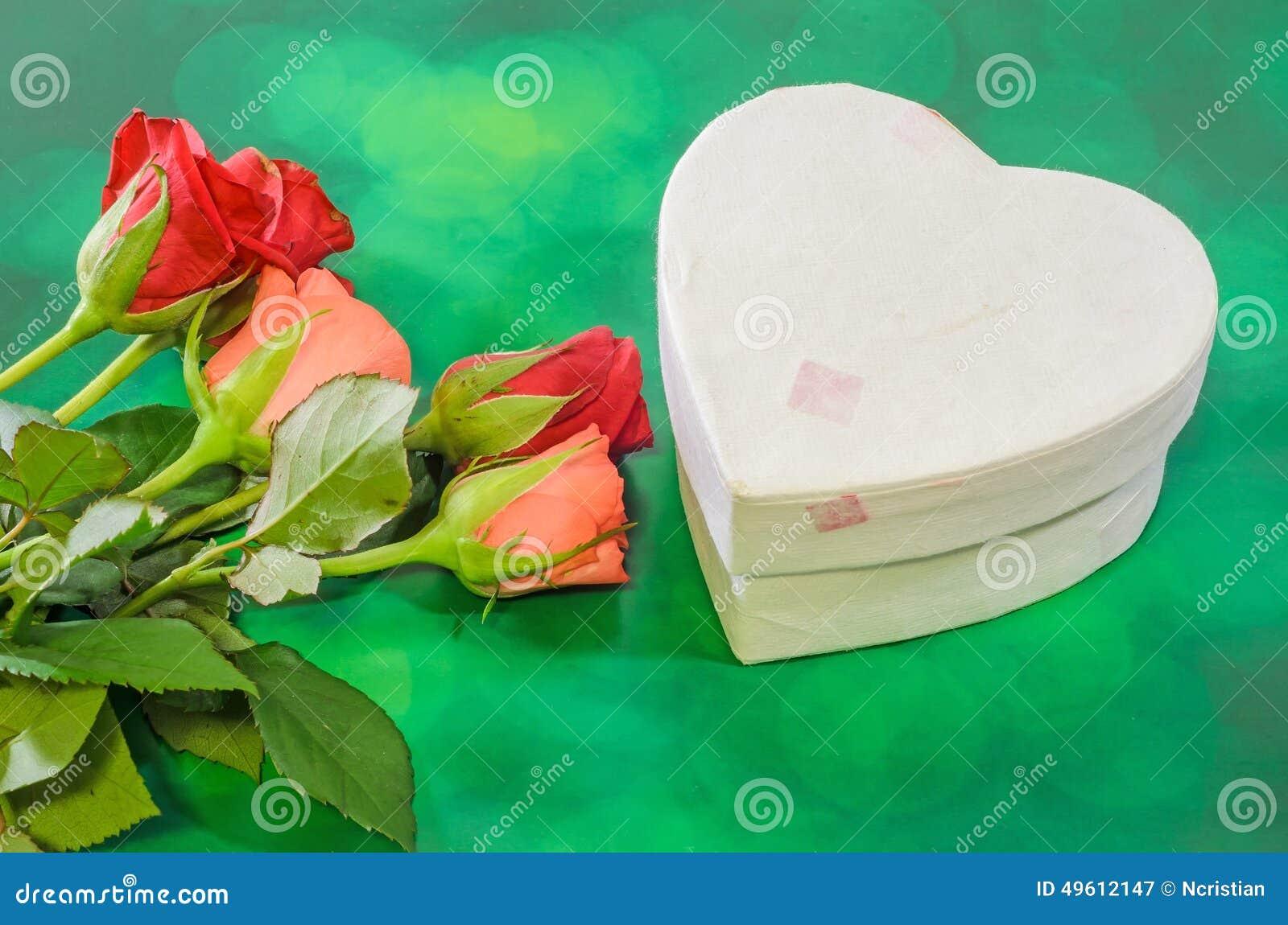 Τα κόκκινα και πορτοκαλιά λουλούδια τριαντάφυλλων με το κιβώτιο μορφής καρδιών, ημέρα βαλεντίνων, υπόβαθρο πράσινου φωτός bokeh,