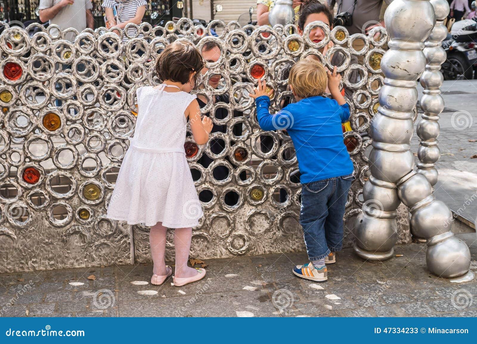 Τα μικρά παιδιά παίζουν το peekaboo με τους γονείς τους μέσω του δαχτυλιδιού
