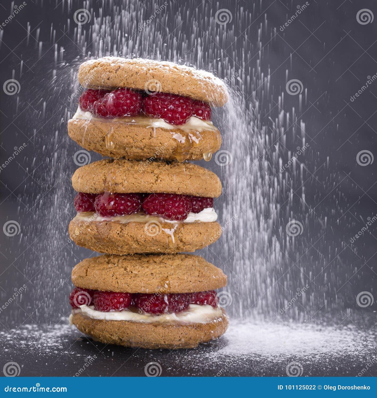 Τα μπισκότα βρωμών με το ακατέργαστο σμέουρο, το μέλι και το μαλακό τυρί στο υπόβαθρο της μαύρης πλάκας, κλείνουν επάνω