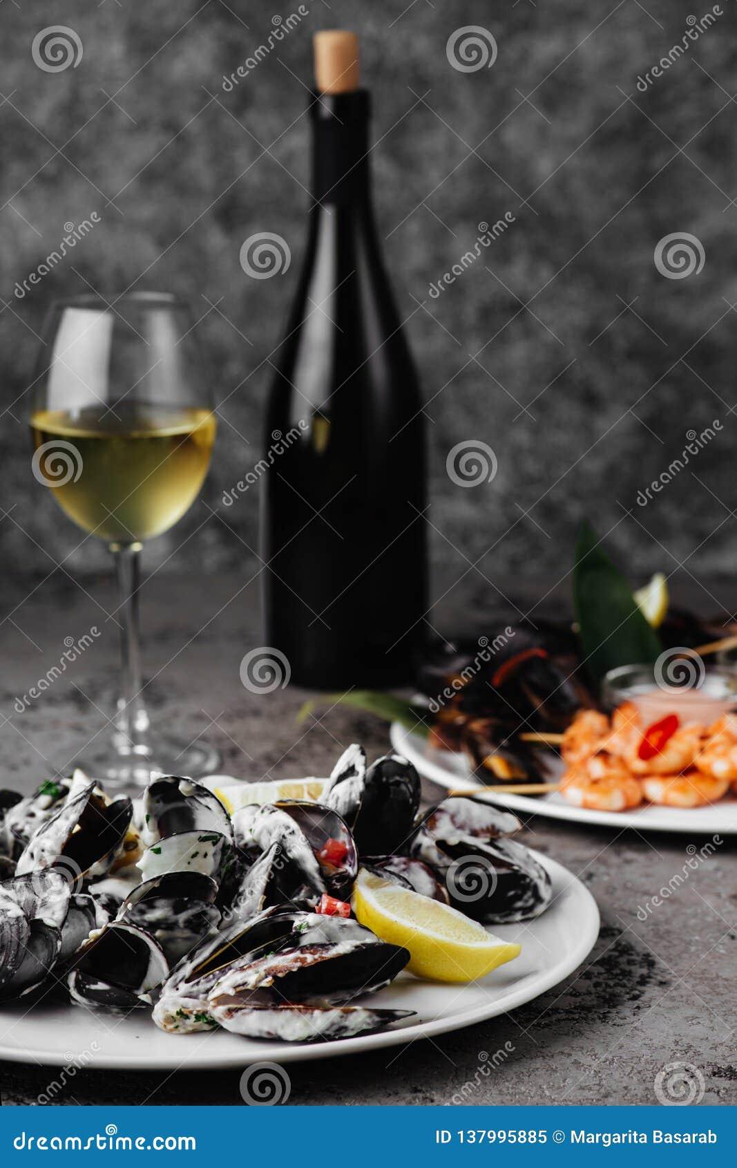 Τα μύδια έβρασαν σε μια σάλτσα του άσπρου κρασιού, που εξυπηρετήθηκε με τη φρυγανιά και το λεμόνι