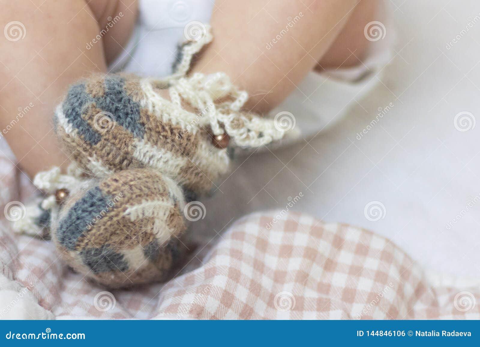 Τα νεογέννητα πόδια μωρών κλείνουν επάνω στις καφετιές πλεκτές λείες καλτσών μαλλιού σε ένα άσπρο κάλυμμα Το μωρό είναι στο παχνί