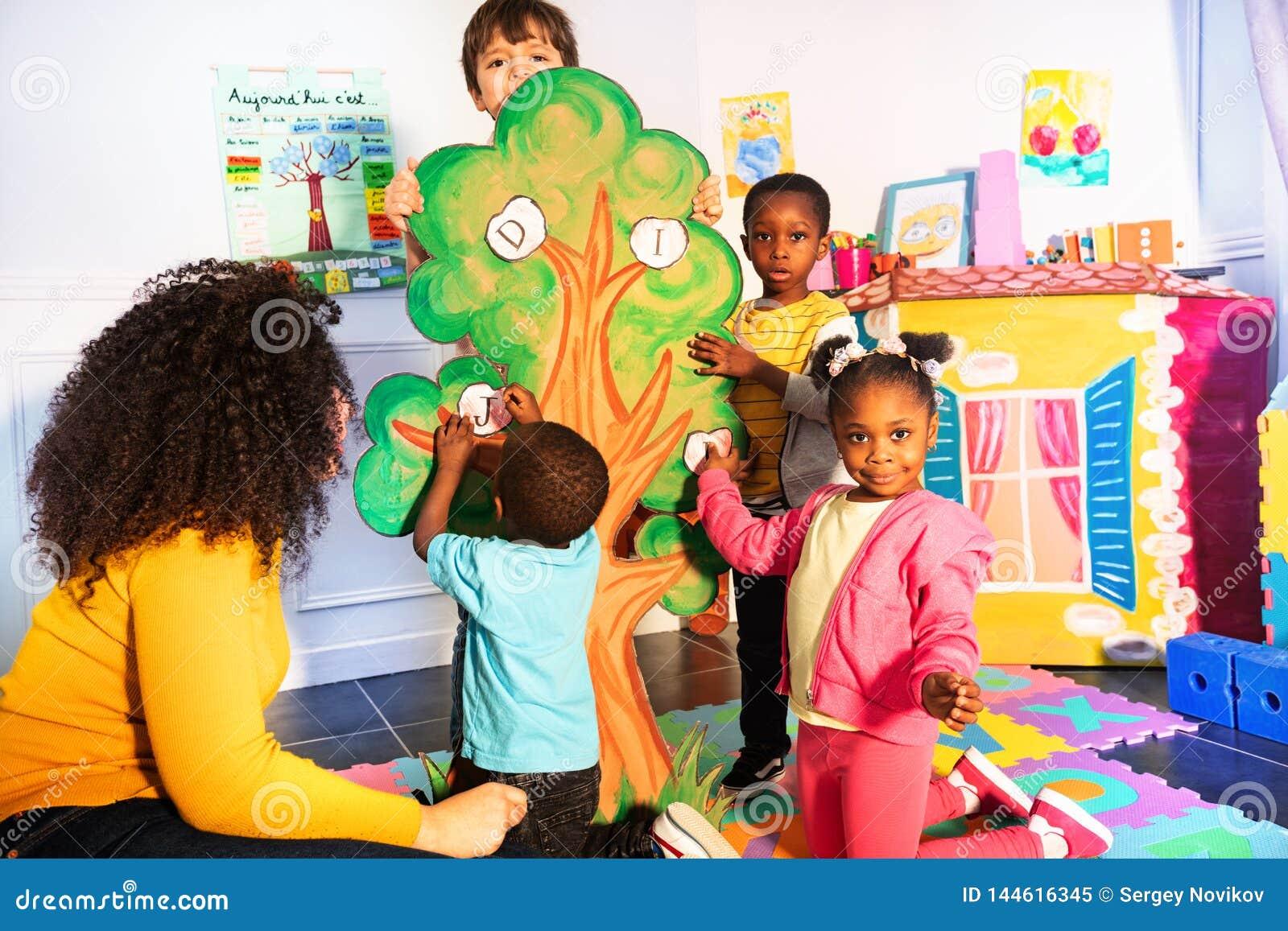 Τα παιδιά μαθαίνουν το αλφάβητο με την τοποθέτηση των επιστολών στο δέντρο