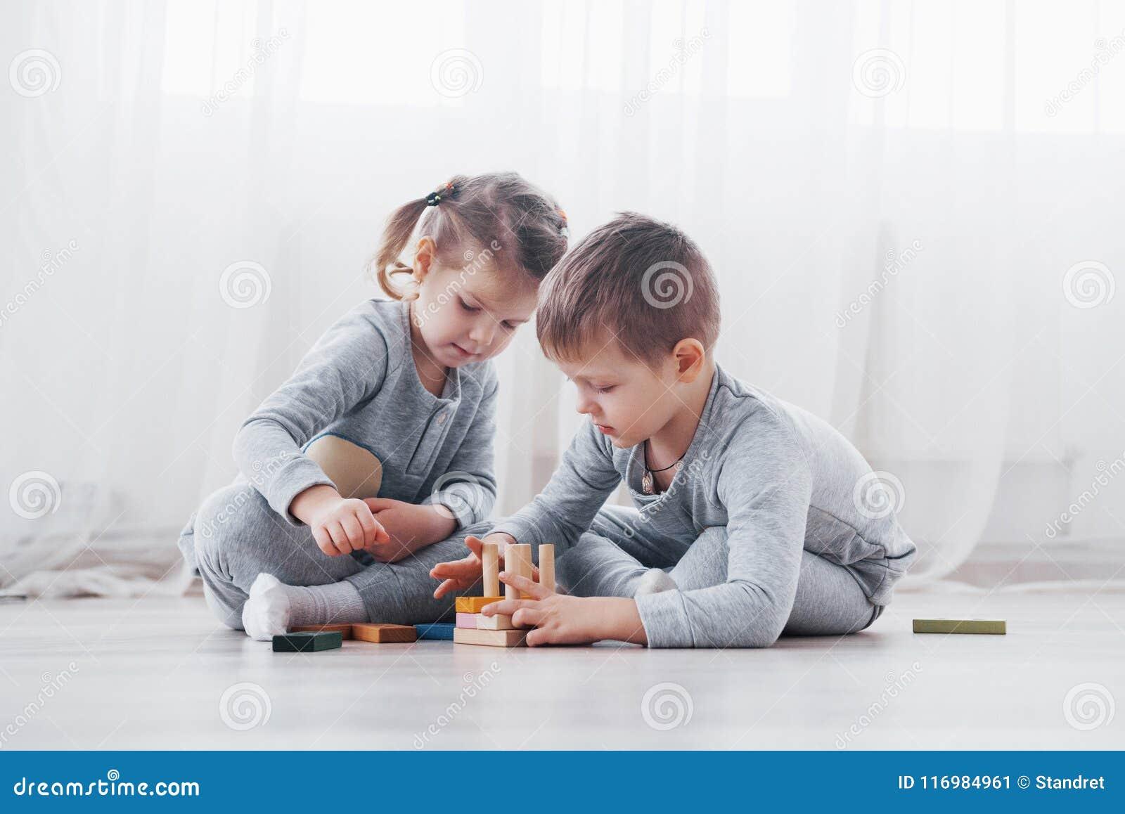 Τα παιδιά παίζουν με έναν σχεδιαστή παιχνιδιών στο πάτωμα του δωματίου παιδιών ` s ζωηρόχρωμα απομονωμένα κατσίκια ομάδων δεδομέν
