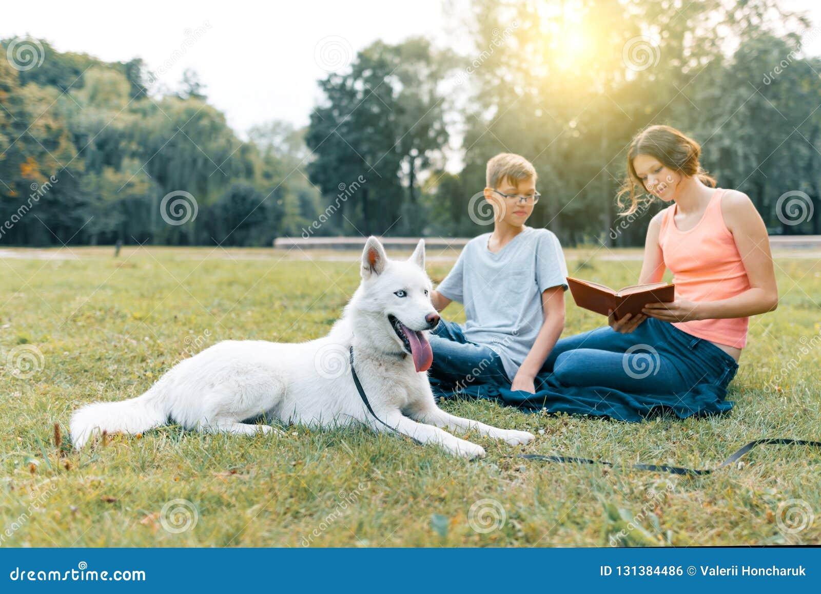 Τα παιδιά στηρίζονται στο πάρκο στον πράσινο χορτοτάπητα με ένα άσπρο σκυλί γεροδεμένο, διαβάζοντας το βιβλίο, ομιλία