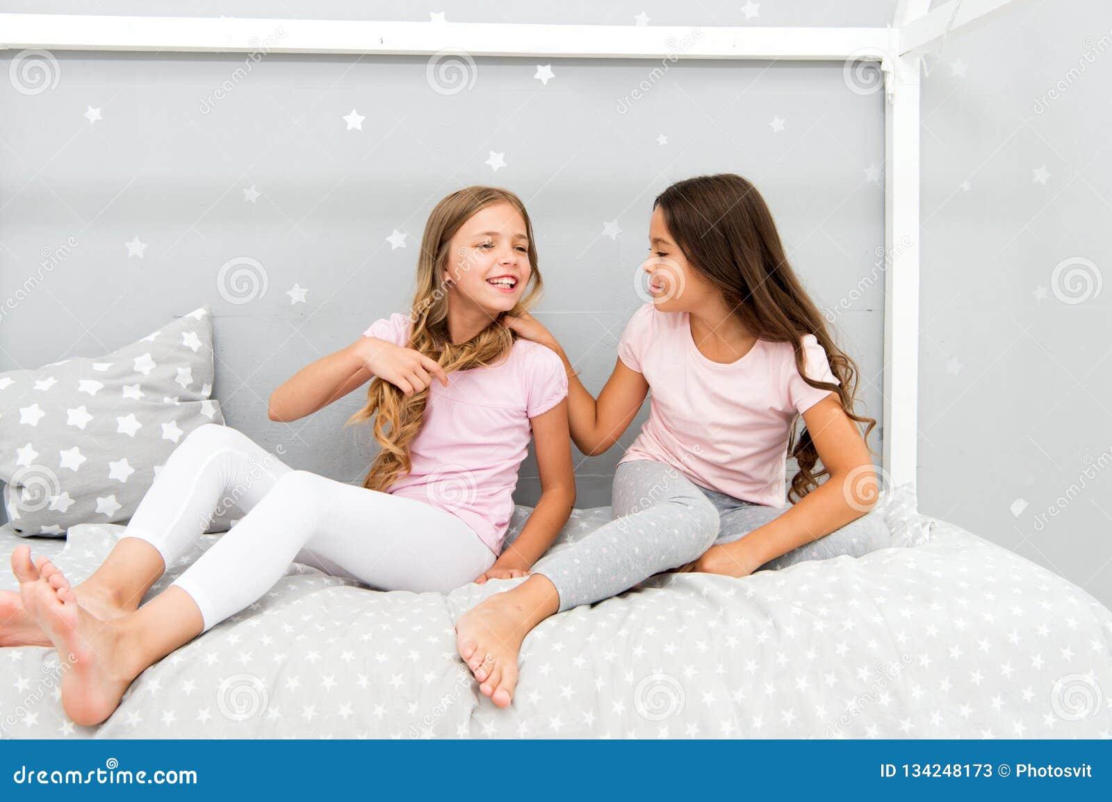 Τα παιδιά χαλαρώνουν και έχοντας τη διασκέδαση το βράδυ Ελεύθερος χρόνος αδελφών Τα κορίτσια στις χαριτωμένες πυτζάμες ξοδεύουν τ