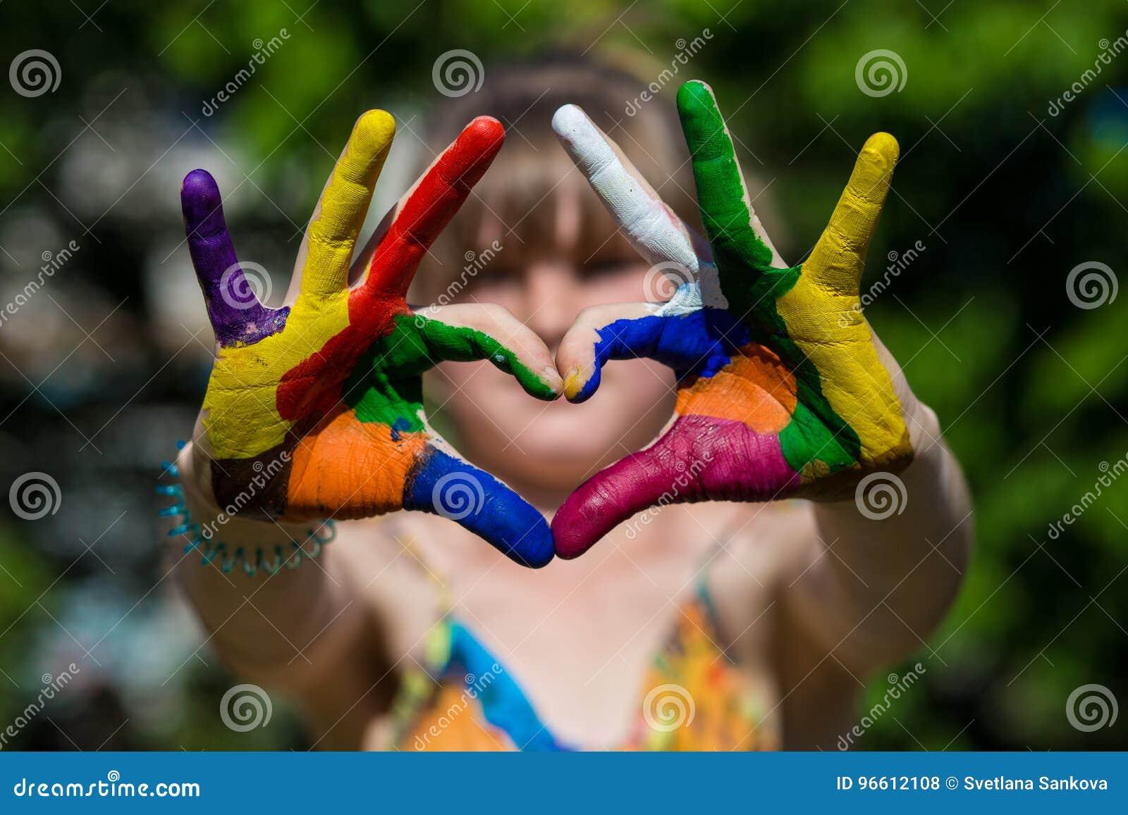 Τα παιδιά παραδίδουν τα χρώματα χρώματος κάνουν μια μορφή καρδιών, εστιάζουν στα χέρια