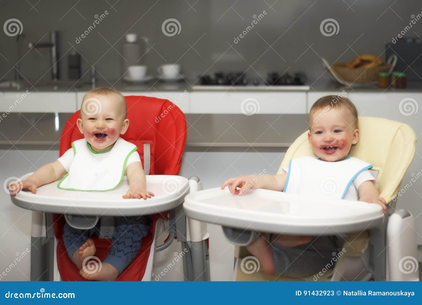 Τα παιδιά τρώνε τα βακκίνια σε μια υψηλή καρέκλα μωρών Τα αγόρια έχουν ένα βρώμικο πρόσωπο
