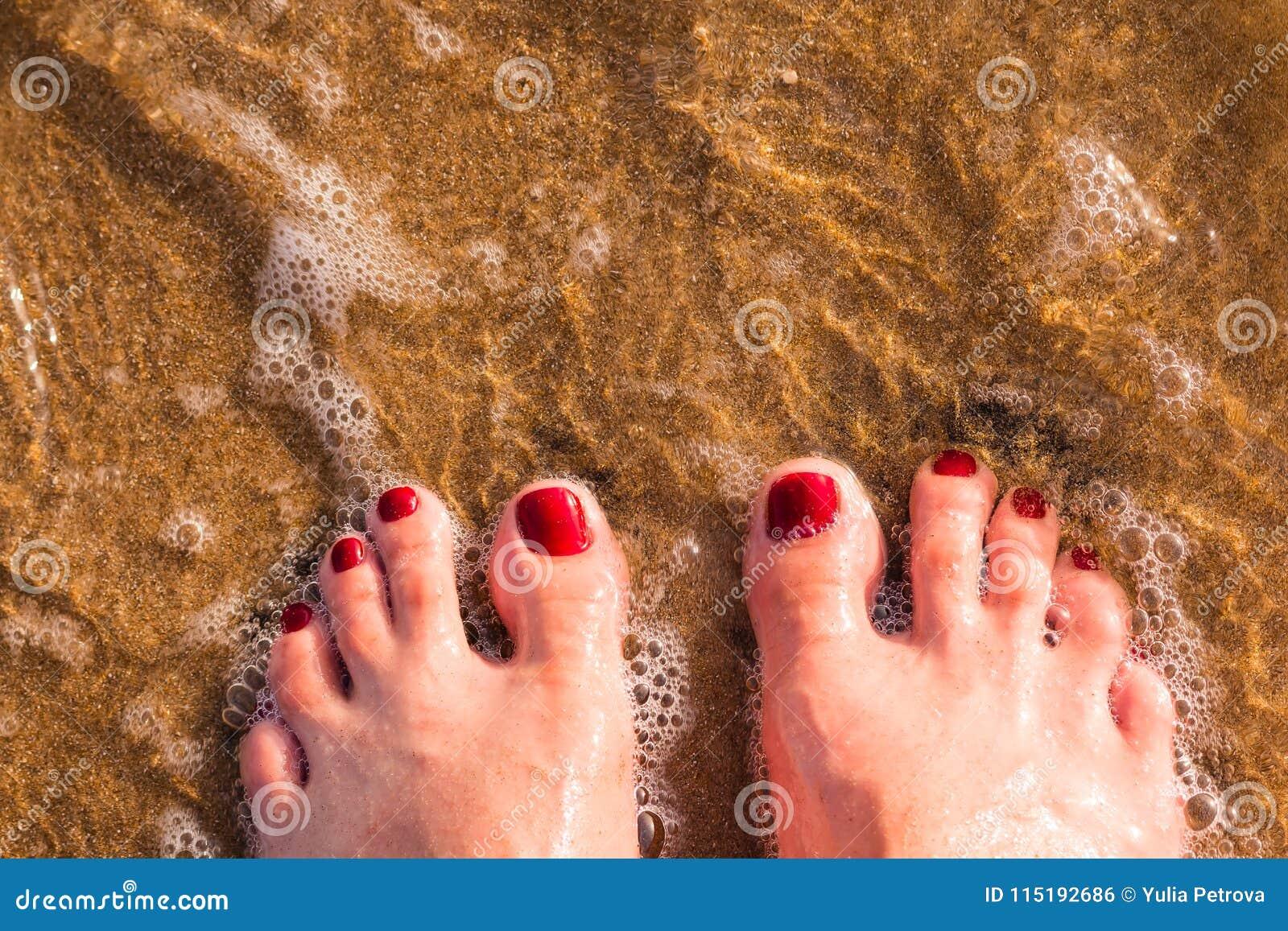2c21fe5292 Τα πόδια γυναικών ` s φορούν τα τζιν με τη γυμνή στάση ποδιών στην άμμο  στην παραλία