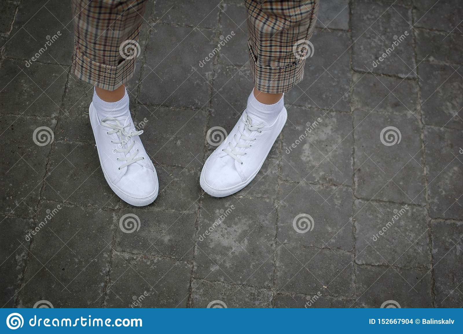 Τα πόδια των γυναικών με τα άσπρα πάνινα παπούτσια και bringht ασθμαίνουν στο δρόμο κατά τη διάρκεια του χρόνου άνοιξης ή καλοκαι
