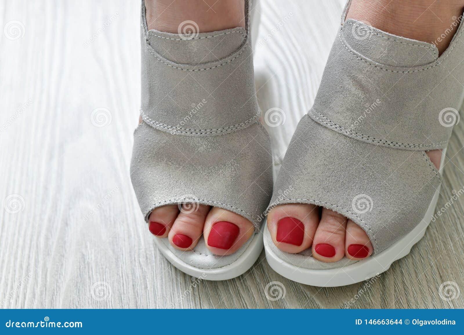 Τα πόδια των γυναικών στα θερινά άσπρα σανδάλια