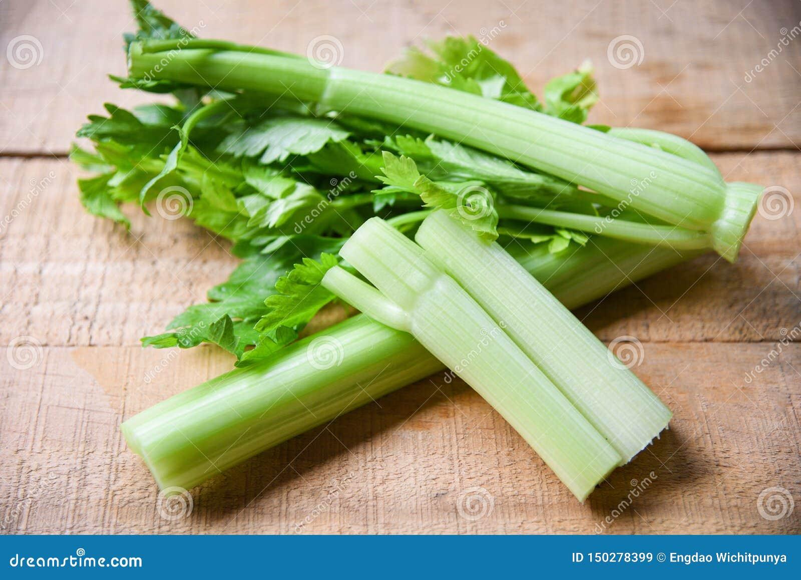 Τα ραβδιά σέλινου και βγάζουν φύλλα το φρέσκο λαχανικό - δέσμη του μίσχου σέλινου στο ξύλινο υπόβαθρο