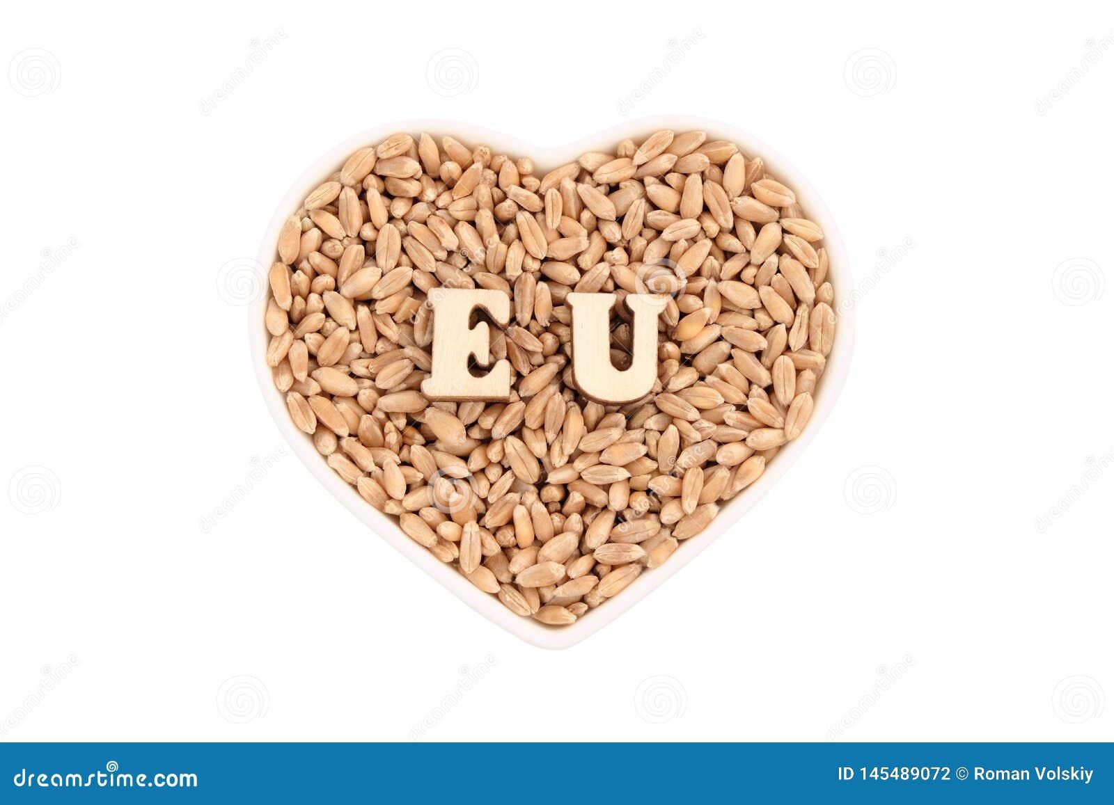 Τα σιτάρια σίτου βρίσκονται σε ένα καρδιά-διαμορφωμένο πιάτο ΕΕ των ξύλινων επιστολών στο σιτάρι r Η έννοια της εισαγωγής και της