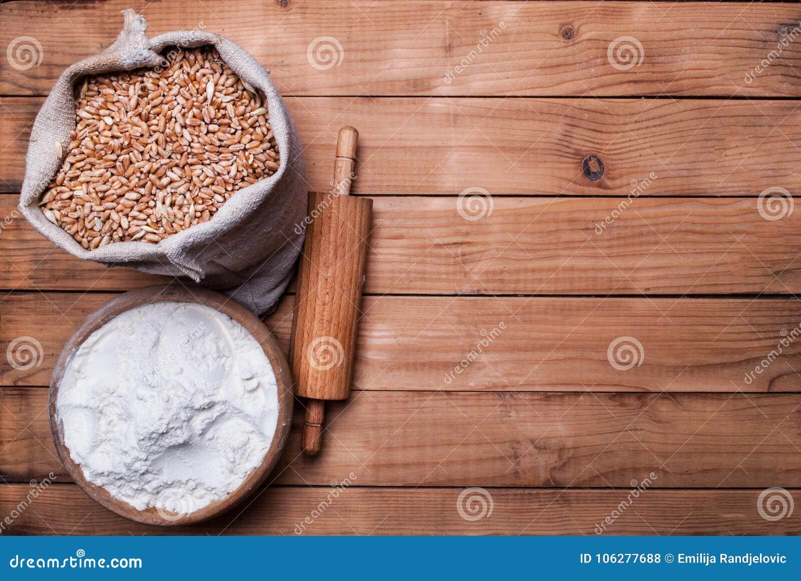 Τα σιτάρια σίτου burlap τοποθετούν σε σάκκο και άσπρο αλεύρι στο κύπελλο και κυλώντας καρφίτσα στο ξύλινο γραφείο