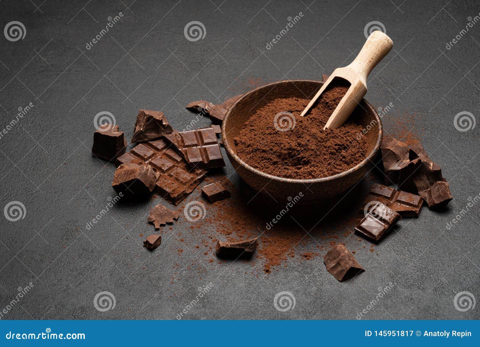 Τα σκοτεινά χοντρά κομμάτια και το κακάο σοκολάτας κονιοποιούν στην ξύλινη σέσουλα στο σκοτεινό συγκεκριμένο υπόβαθρο