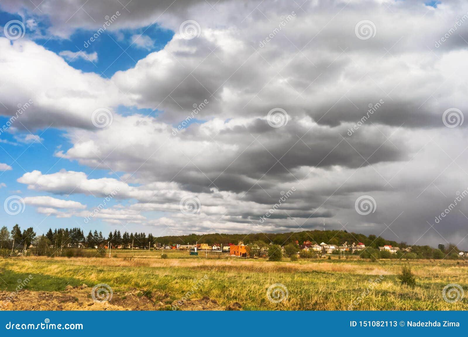 Τα σύννεφα κλείνουν τον ήλιο, σύννεφα θύελλας πέρα από το χωριό