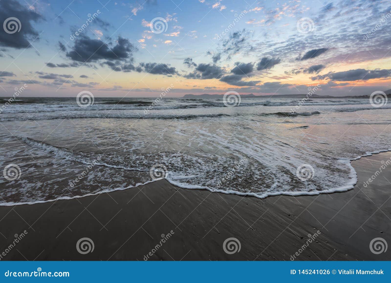 Τα υψηλά κύματα με τον αφρό διαδίδουν στην άμμο στην ακτή που το φως του απίστευτου ηλιοβασιλέματος απεικονίζει στη θάλασσα Βουνά
